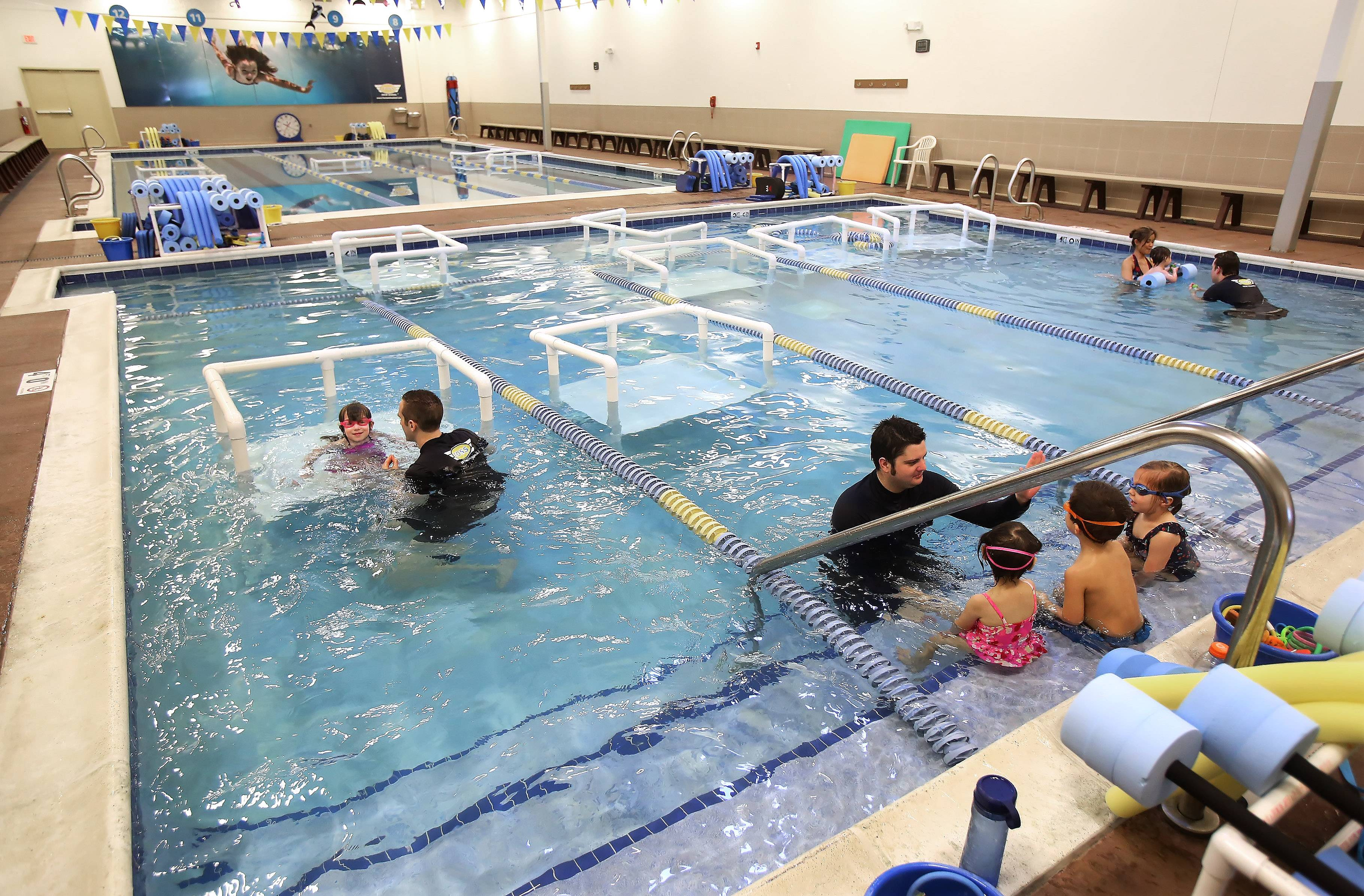 Swim instructors work with young children as they learn to swim at FOSS Swim School in Highland Park.