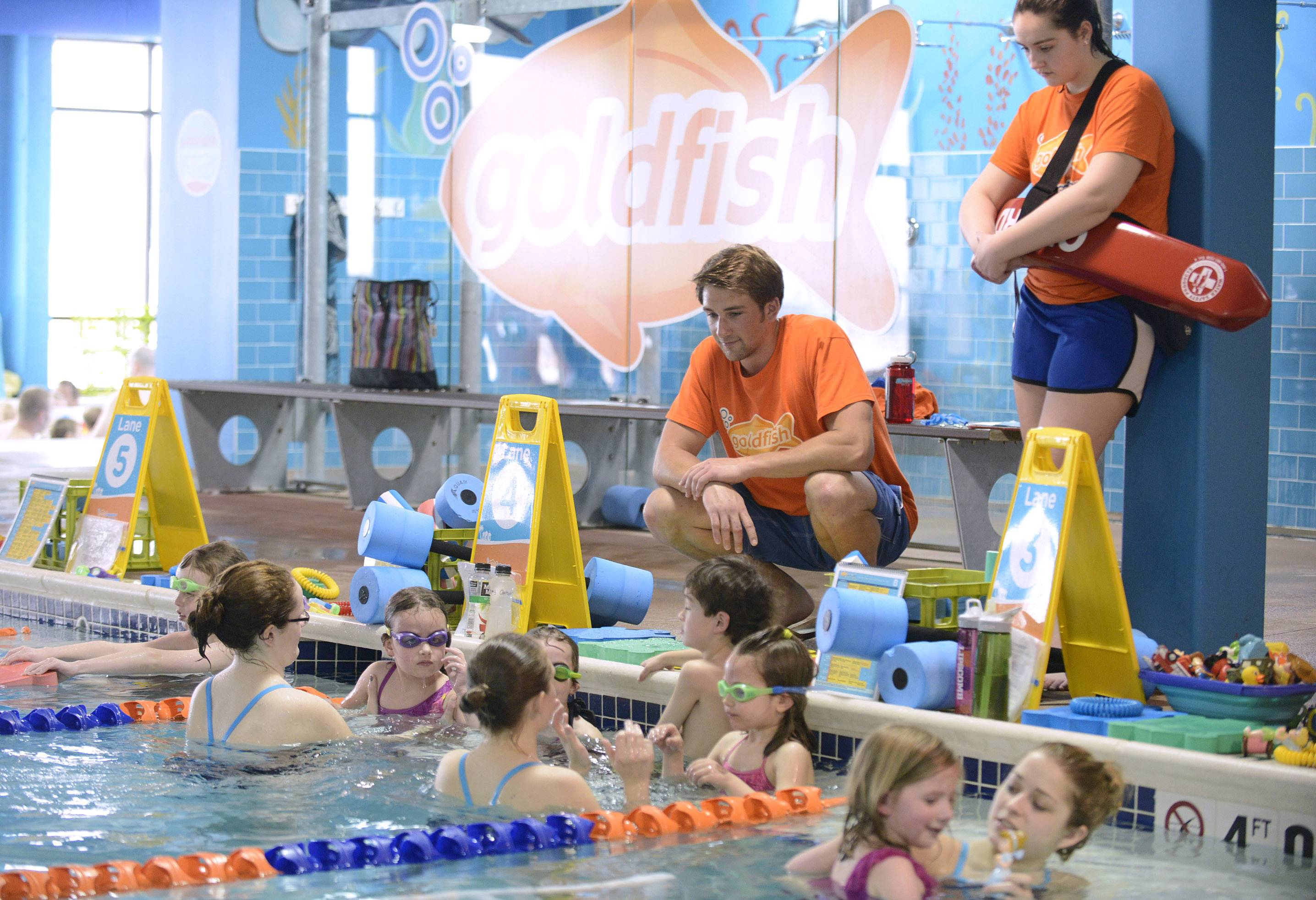 Goldfish Swim School owner Alex Tyler, squatting, chats with students and instructors during Saturday morning classes the St. Charles school.