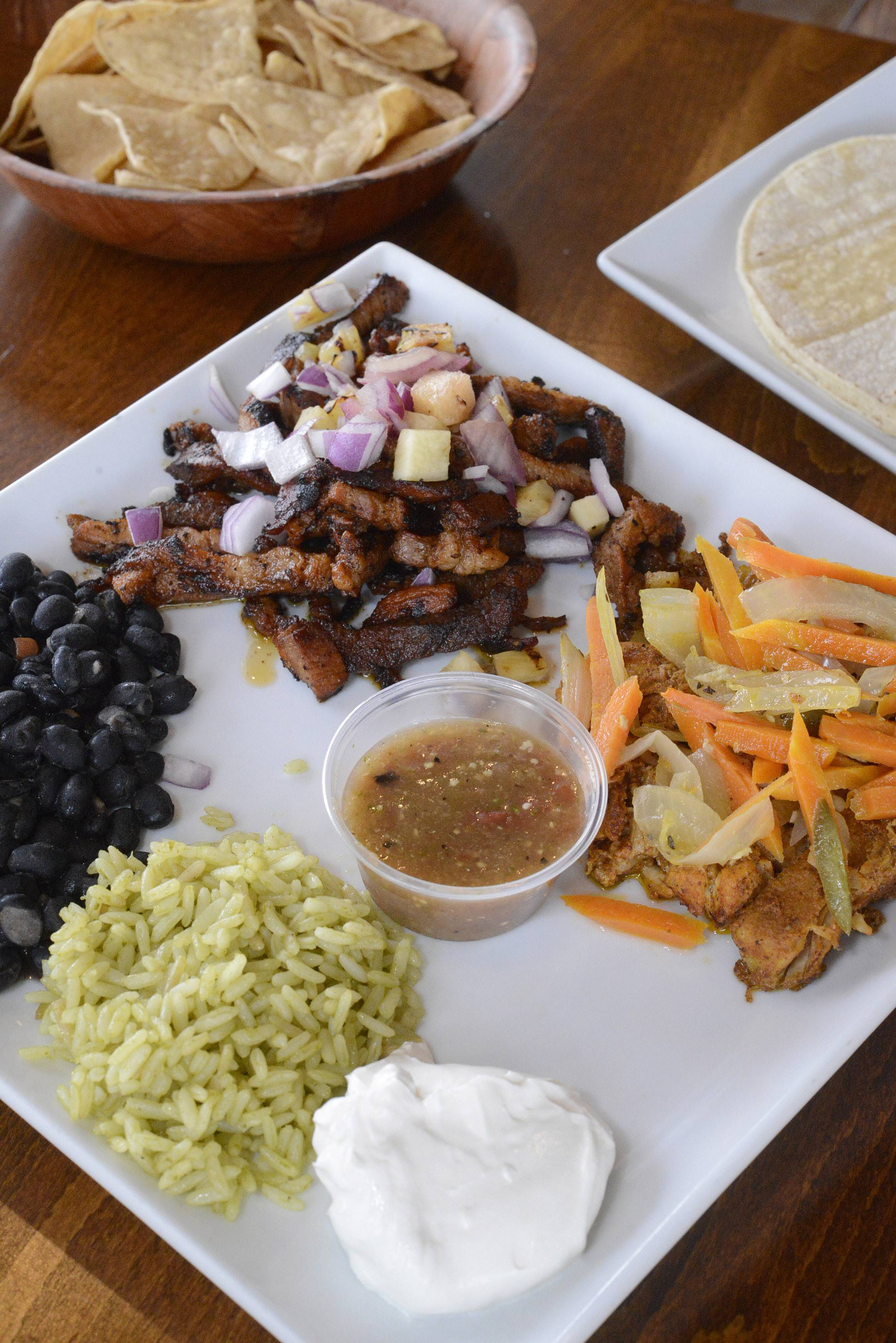 Cactus Zone's pork platter pairs pork tenderloin topped with pineapple salsa, right, with slow-cooked pork called cochinita pibil.