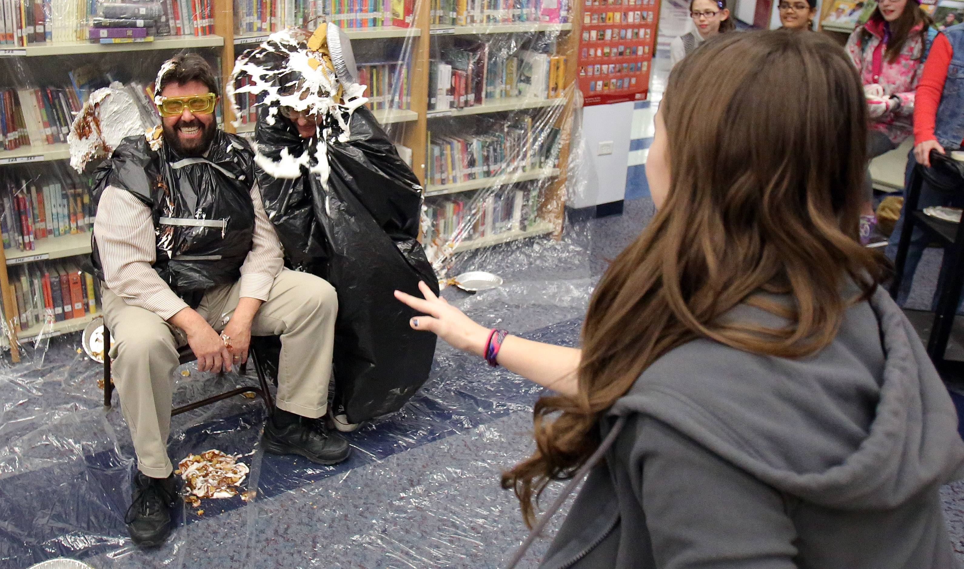 Frederick School Librarian Robert Depke, left, and Assistant Principal Jodi Cinq-Mars have a pie thrown at them by sixth-grader Madyson Russo Wednesday. Grayslake students who read 20 books as part of the Rebecca Caudill Young Readers Book program had the honor of throwing pies.