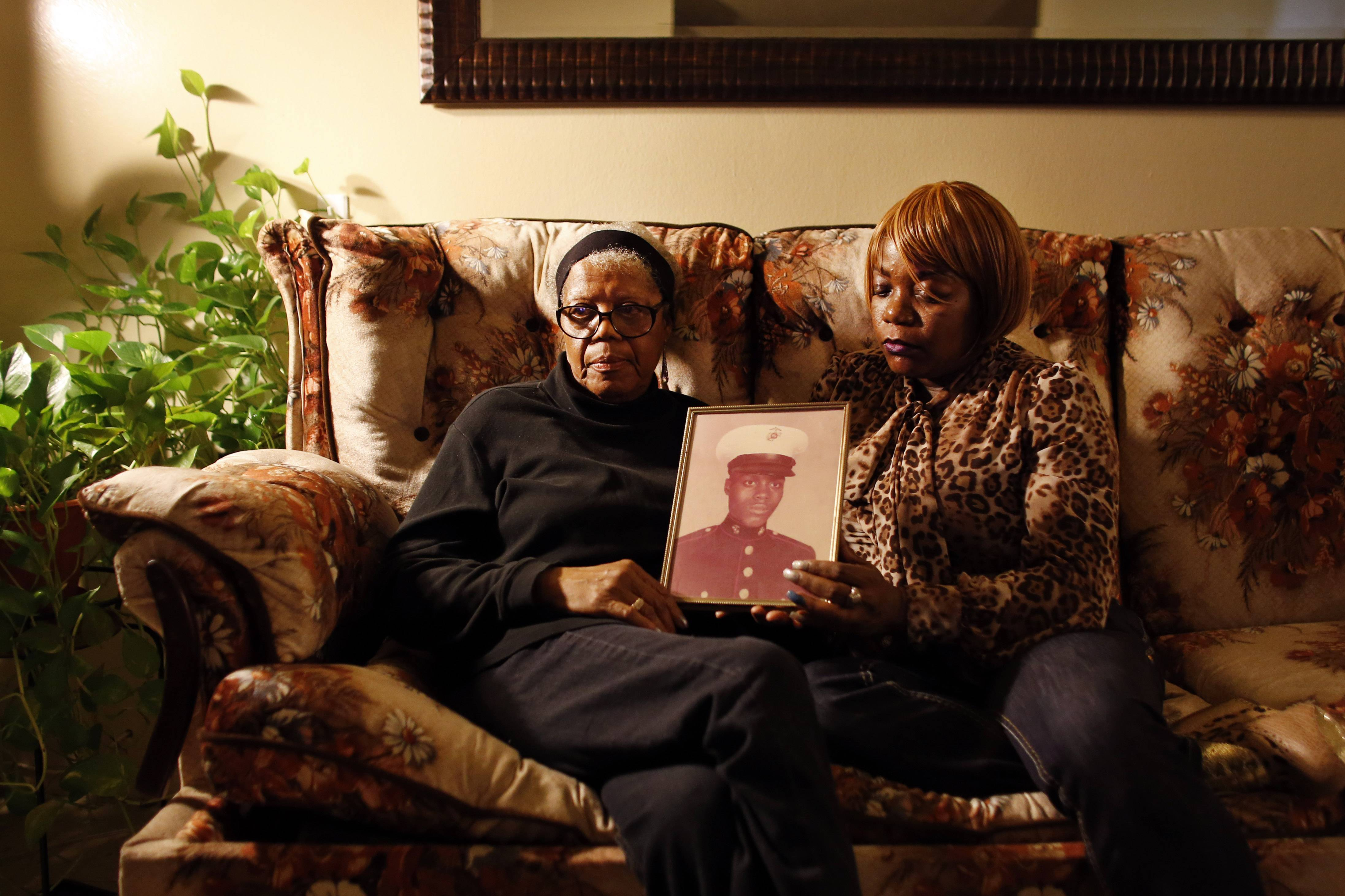 Alma Murdough and her daughter Cheryl Warner hold a photo of Murdough's son, at her home in the Queens borough of New York. Jerome Murdough, a mentally ill, homeless former Marine arrested for sleeping in the roof landing of a New York City public housing project, died last month in a Rikers Island jail cell that officials say was at least 100 degrees when his body was discovered.