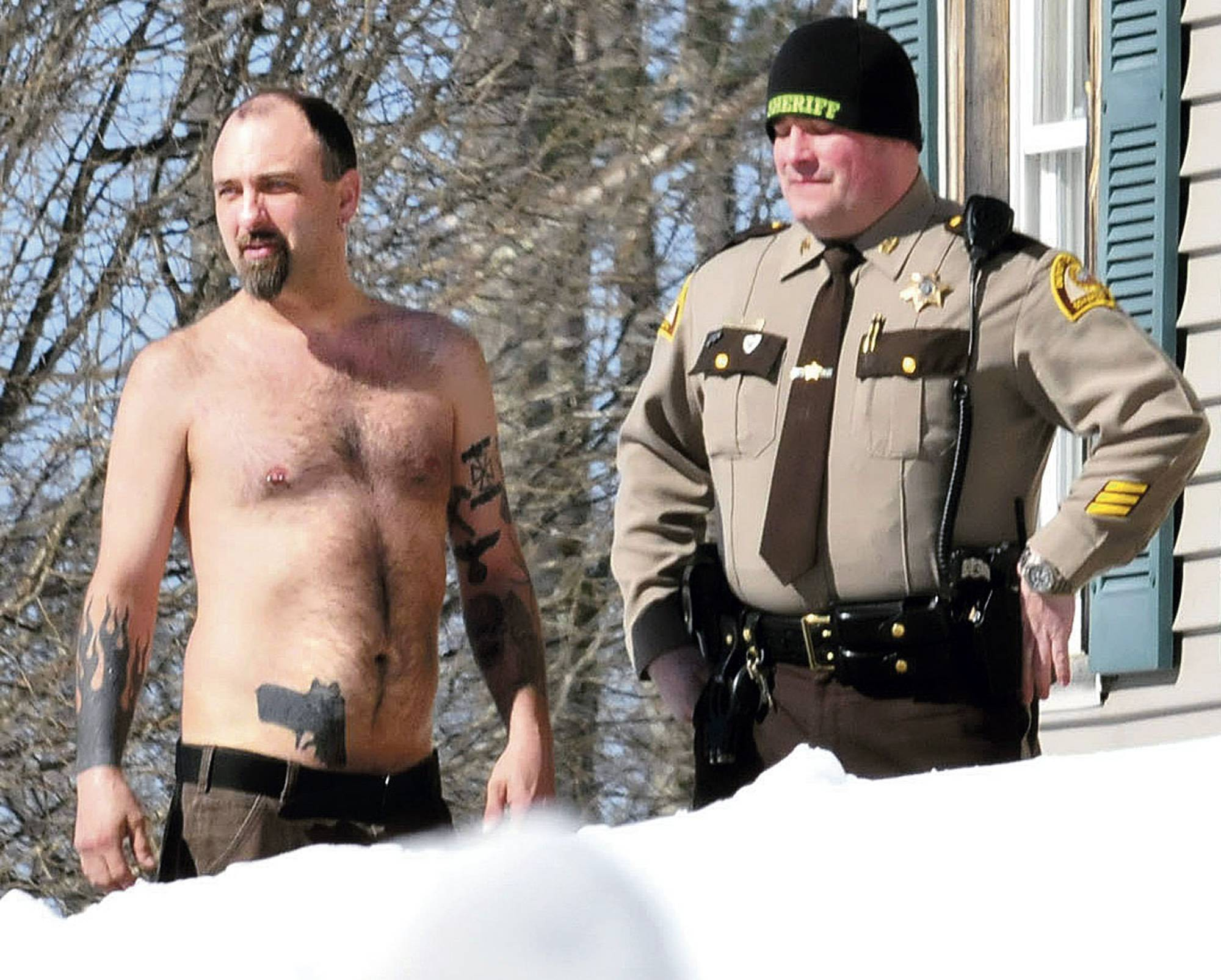 "Michael Smith, left, stands beside a Somerset County Sheriff deputy outside his home in Norridgewock, Maine. Officers armed with assault rifles descended on Smith's home after members of a tree removal crew he'd told to clear off his property reported that he had a gun. The ""gun"" the tree crew had seen on Smith actually was a life-sized tattoo of a handgun on his stomach."