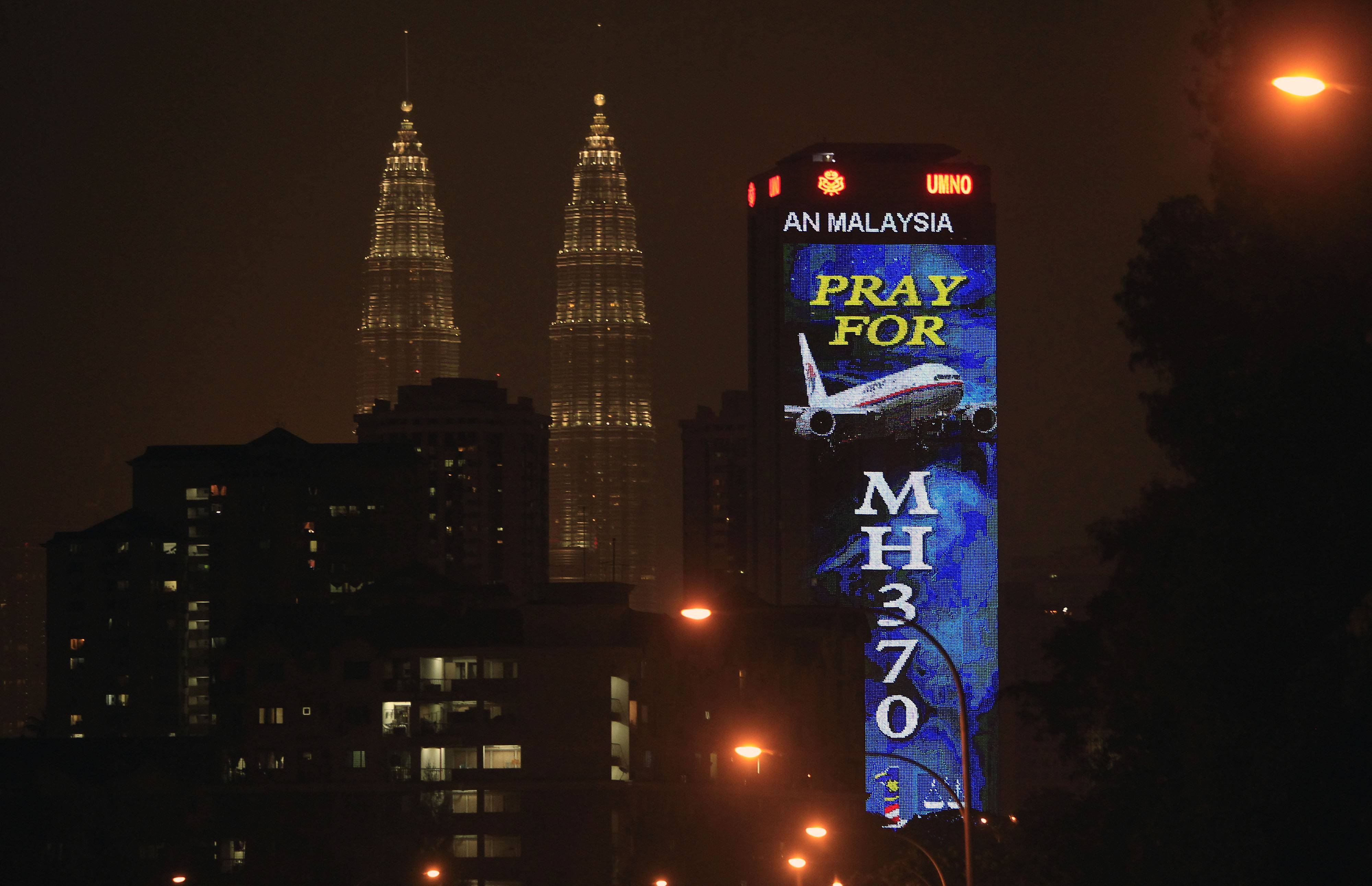"An office building is illuminated with LED lights displaying ""Pray for MH370"" next to Malaysia's landmark Petronas Twin Towers in Kuala Lumpur, Malaysia, Wednesday, March 19, 2014."