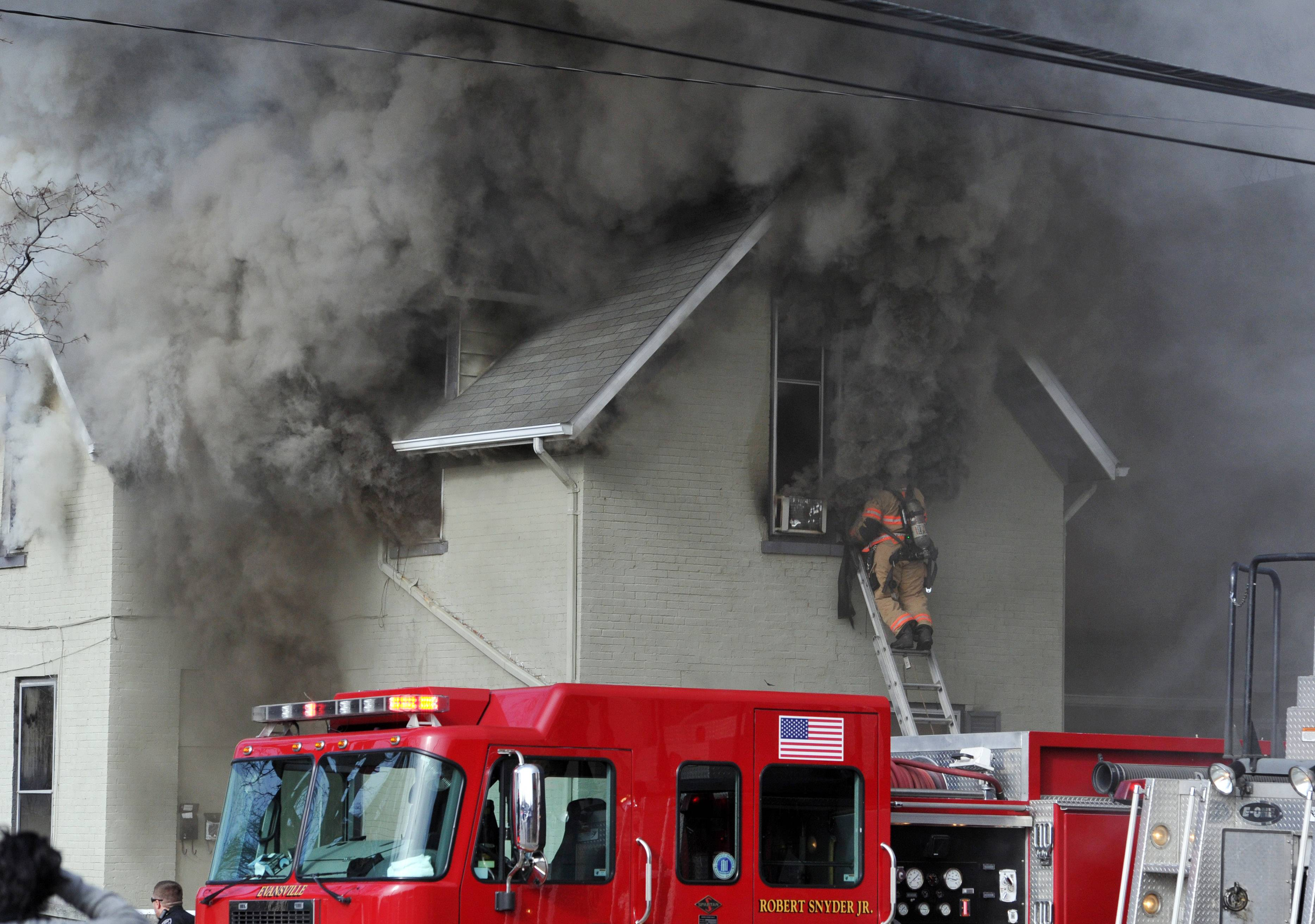 An Evansville firefighter uses a ladder to try to quickly access the second floor of a burning apartment on W. Franklin Street near the N. Baker Avenue intersection in Evansville, Ind. Three people died and eight others were injured in the fire, which authorities are investigating as a possible arson.