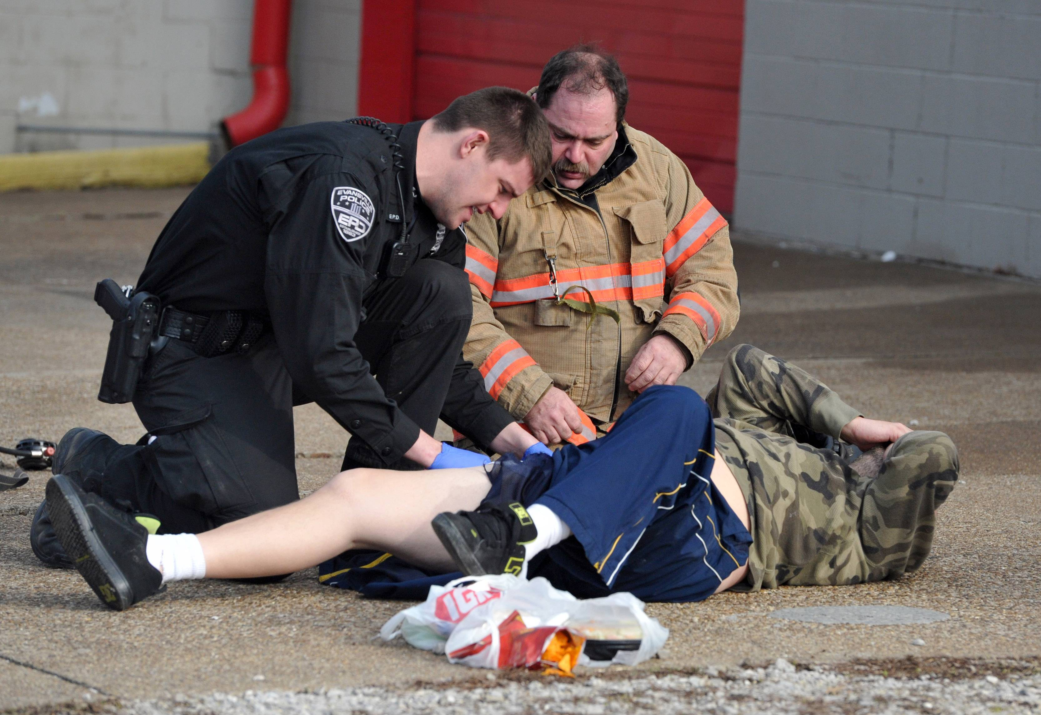 Evansville police Officer Nathan Hassler and an Evansville firefighter tend to a victim of an apartment fire in Evansville, Ind., Monday, March 17, 2014. Three people died and eight others were injured in the fire.