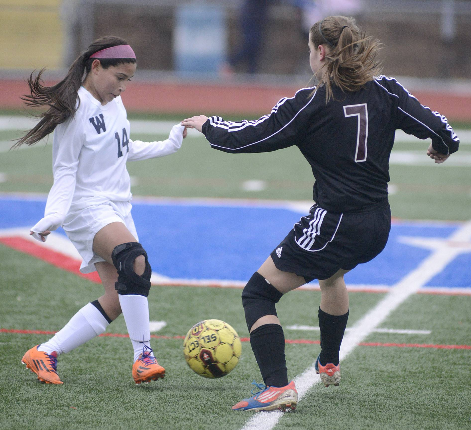 West Aurora's Jocelyn Ferrar, left, and Wheaton Academy's Jamie Netzley fight for the ball in the first half on Wednesday in Aurora.