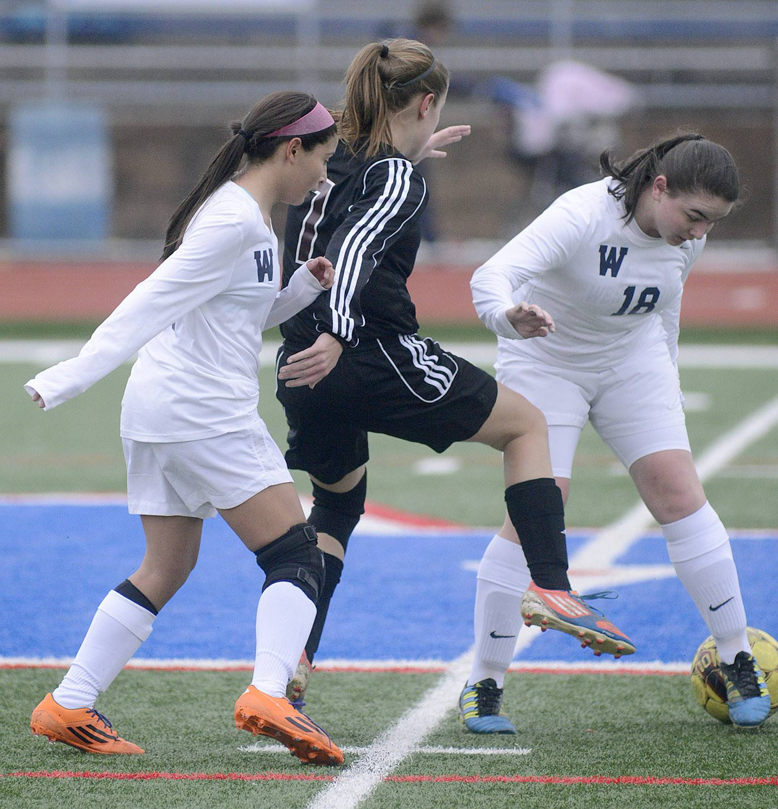 West Aurora's Jocelyn Ferrar, left, and Alicia Rotolo, far right, sandwich Wheaton Academy's Jamie Netzley as they try to keep control of the ball in the first half on Wednesday, March 19.