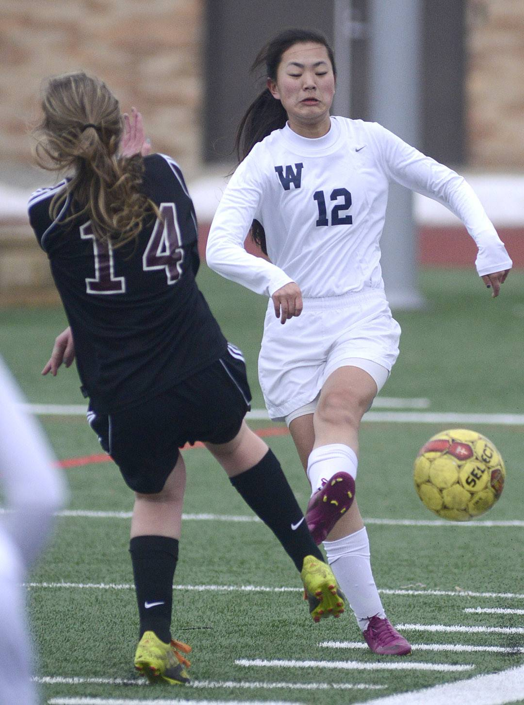 West Aurora's Carli Hix drives the ball past Wheaton Academy's Kate Lindsay in the first half on Wednesday, March 19.