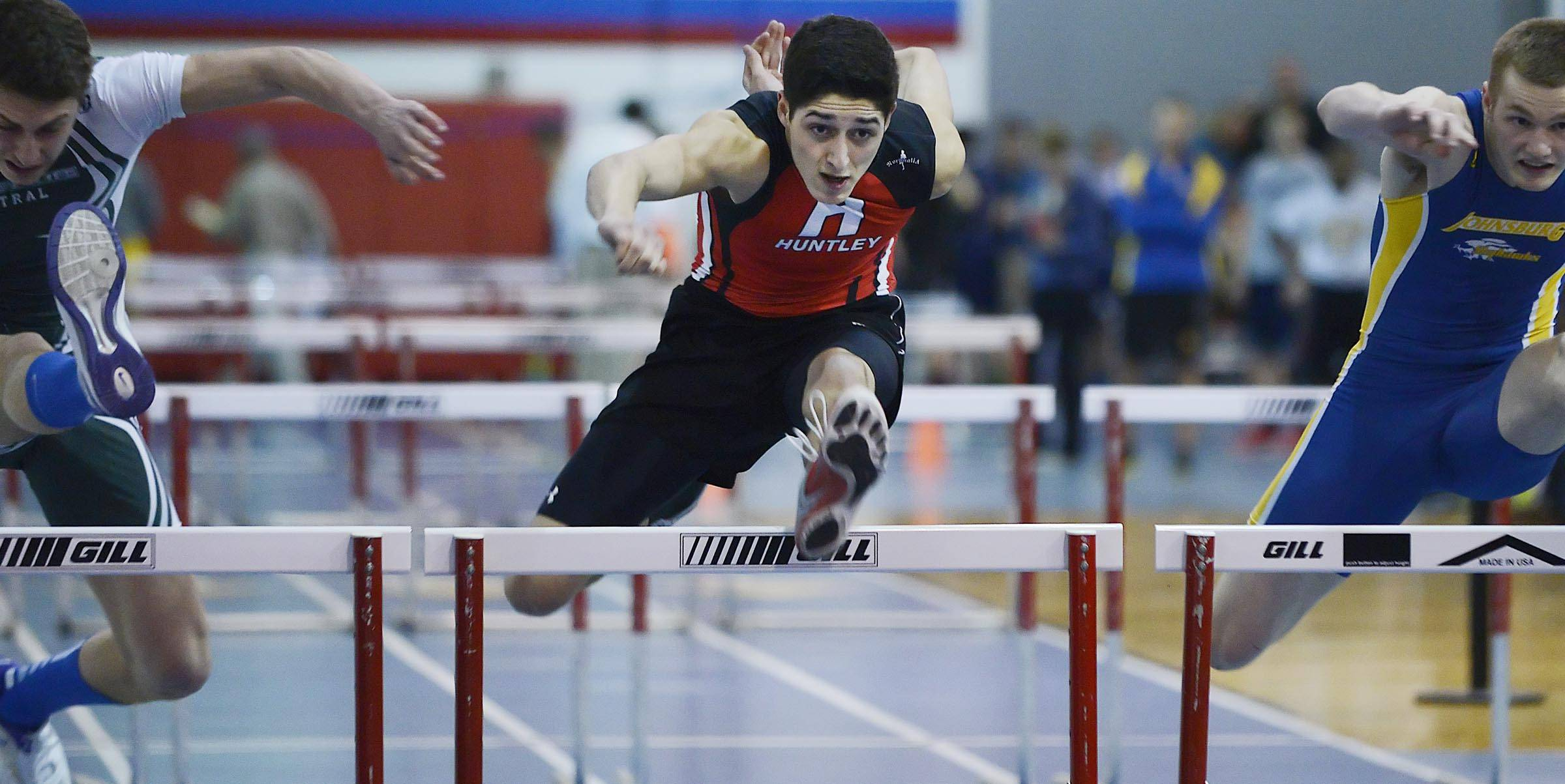 Huntley's Brennen Bell comes over the last obstacle on his way to a meet record time in the 55-meter high hurdles Wednesday at the Fox Valley Conference boys indoor track meet at Dundee-Crown High School in Carpentersville.