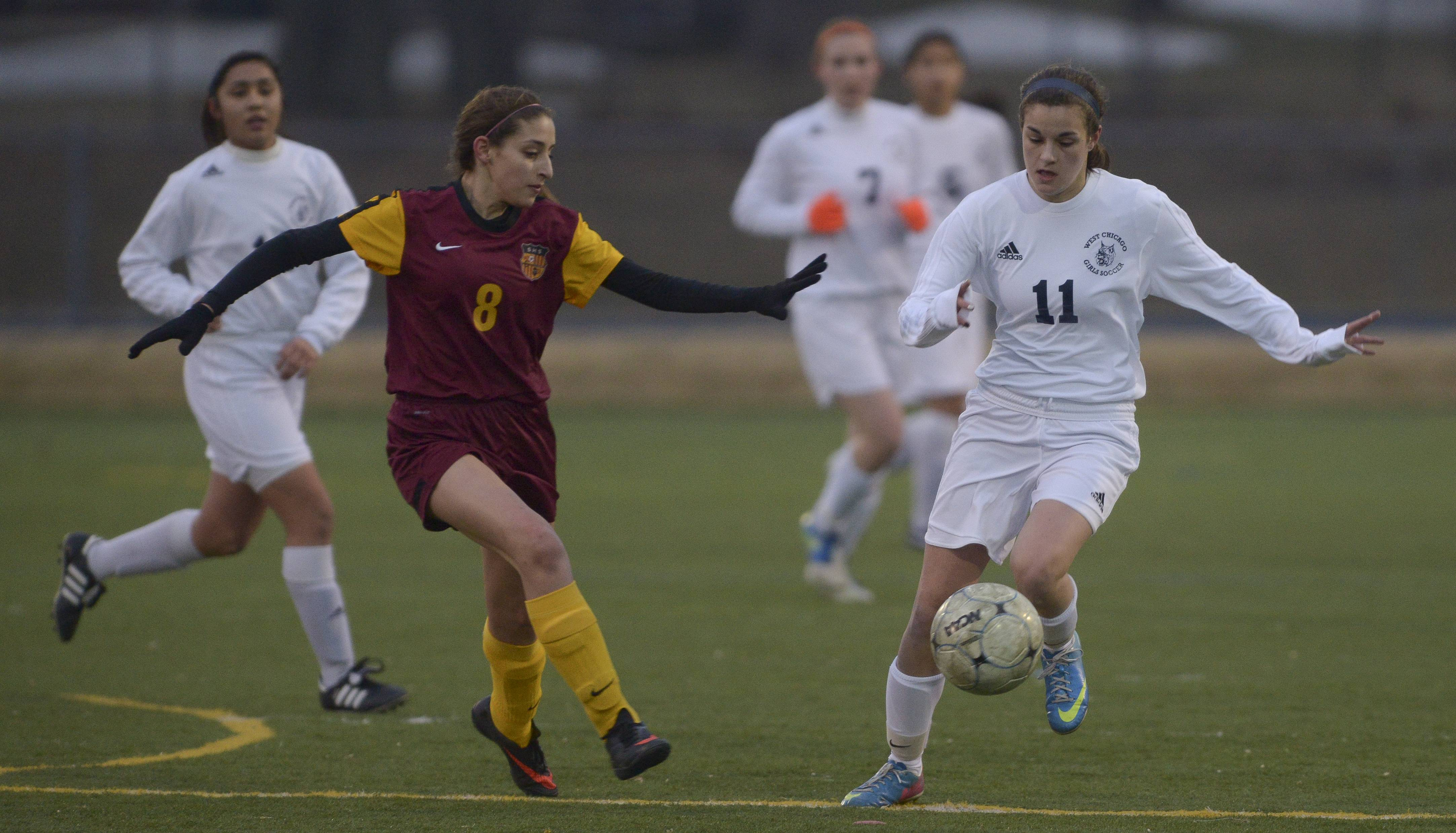Mark Black/mblack@dailyherald.comSchaumburg's Julia Morales and West Chicago's Katie Reitz work for control of the ball during varsity girls soccer in West Chicago Wednesday night.