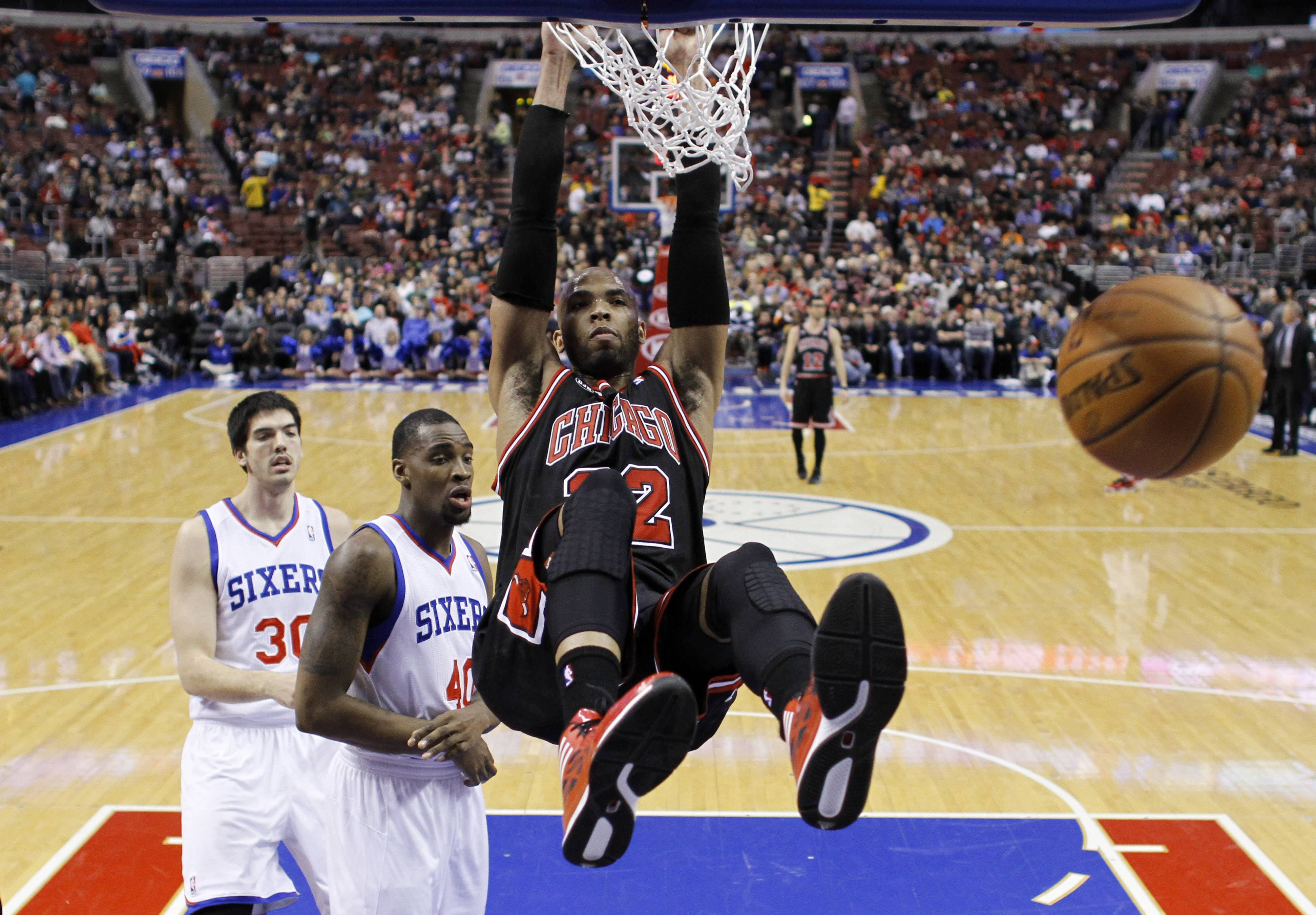 Chicago Bulls' Taj Gibson (22) hangs on the rim after dunking the ball against Philadelphia 76ers' Jarvis Varnado (40) and Byron Mullens (30) during the first half of an NBA basketball game, Wednesday in Philadelphia.
