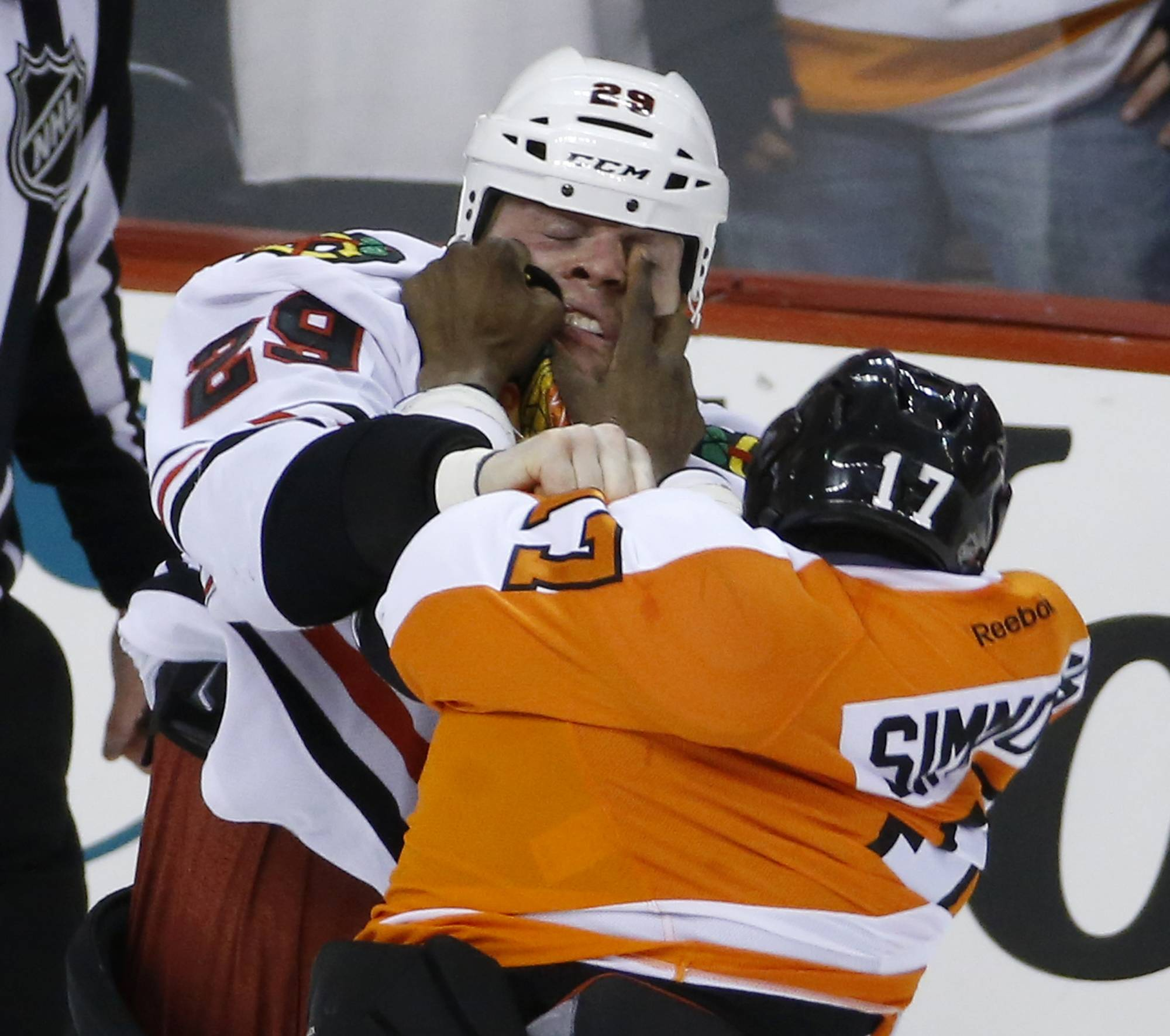 Blackhawks forward Bryan Bickell, left, and the Philadelphia Flyers' Wayne Simmonds fight Tuesday during the third period in Philadelphia. Philadelphia won 3-2 in overtime.