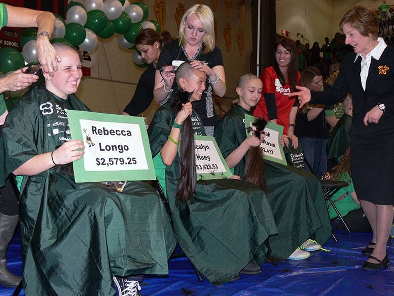 Superintendent Nancy Robb, right, who participated in the Schaumburg High School St. Baldrick's event by donning a green hair extension, shows students support while they shave their heads for St. Baldrick's.