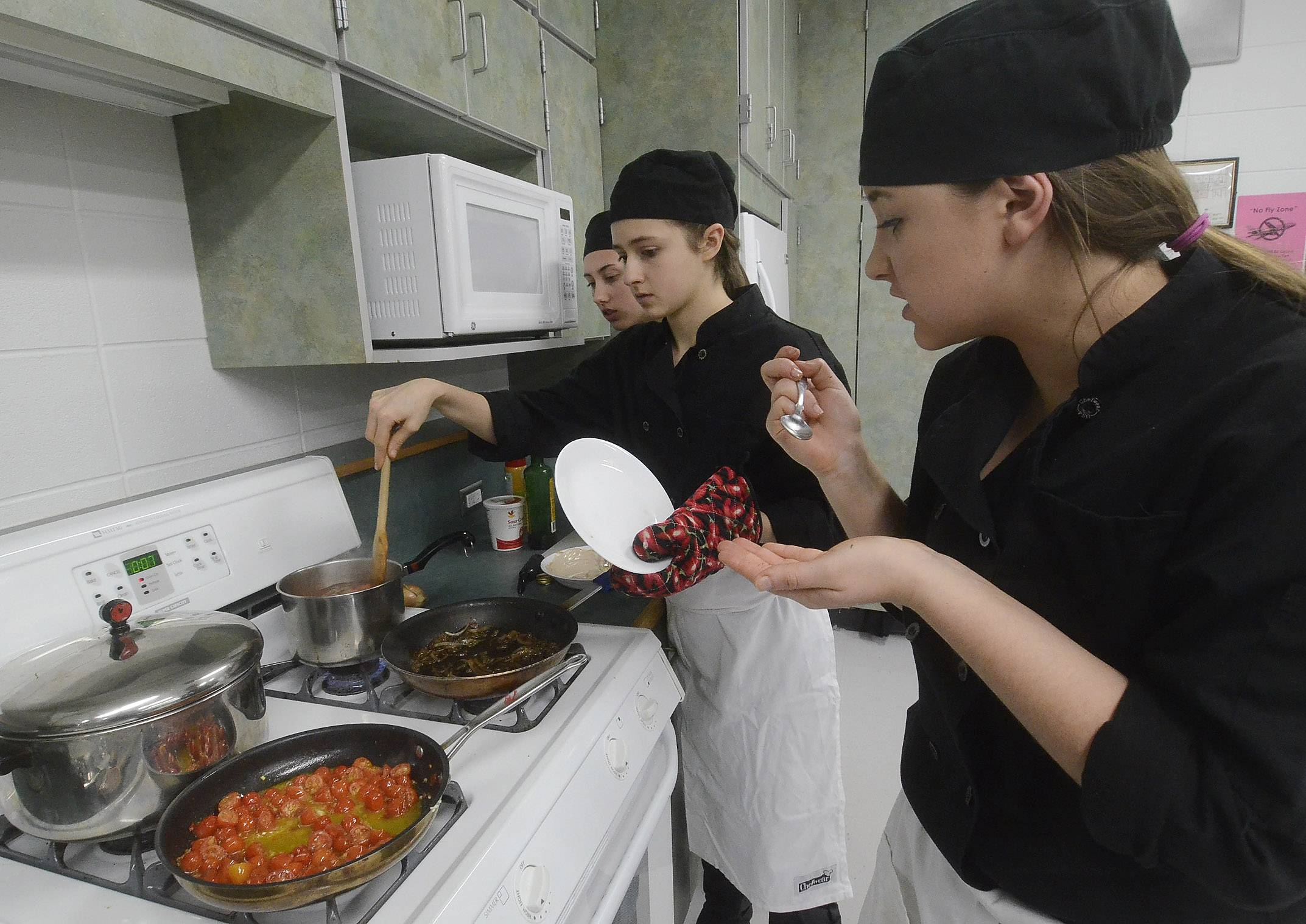 ProStart Team 6 members from left, Tayler Merkel, Madi Woltman and Gina Cirrincione work on their pasta dish during Elk Grove High School's ProStart vs. Faculty Cook-off.