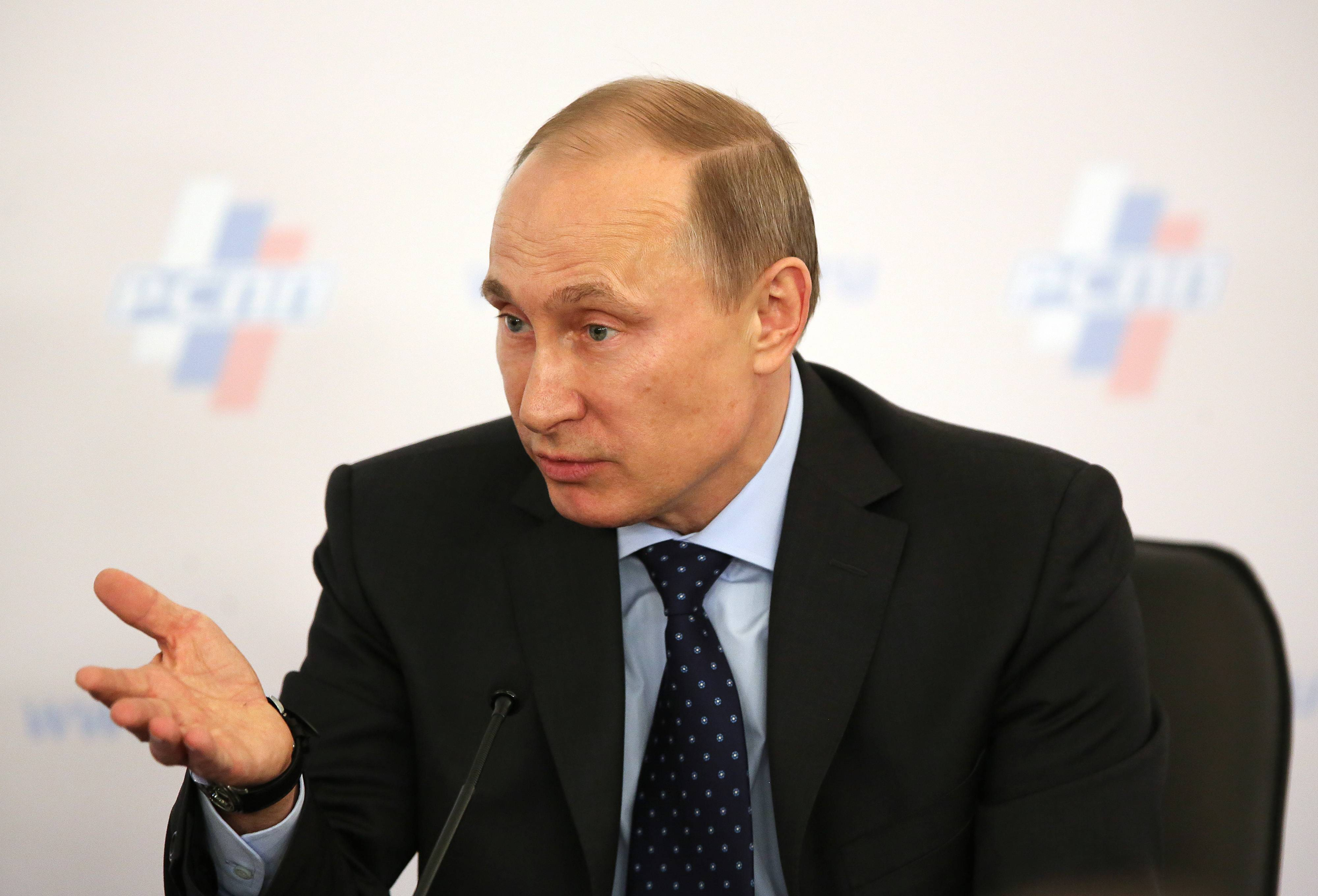 Russian President Vladimir Putin addresses business leaders in Moscow on Thursday. Putin, facing the weakest economic outlook in four years and forecasts of surging capital outflows, is defying Western threats of sanctions and pressing ahead with plans to absorb Crimea, a predominantly Russian-speaking region that houses the Black Sea Fleet.
