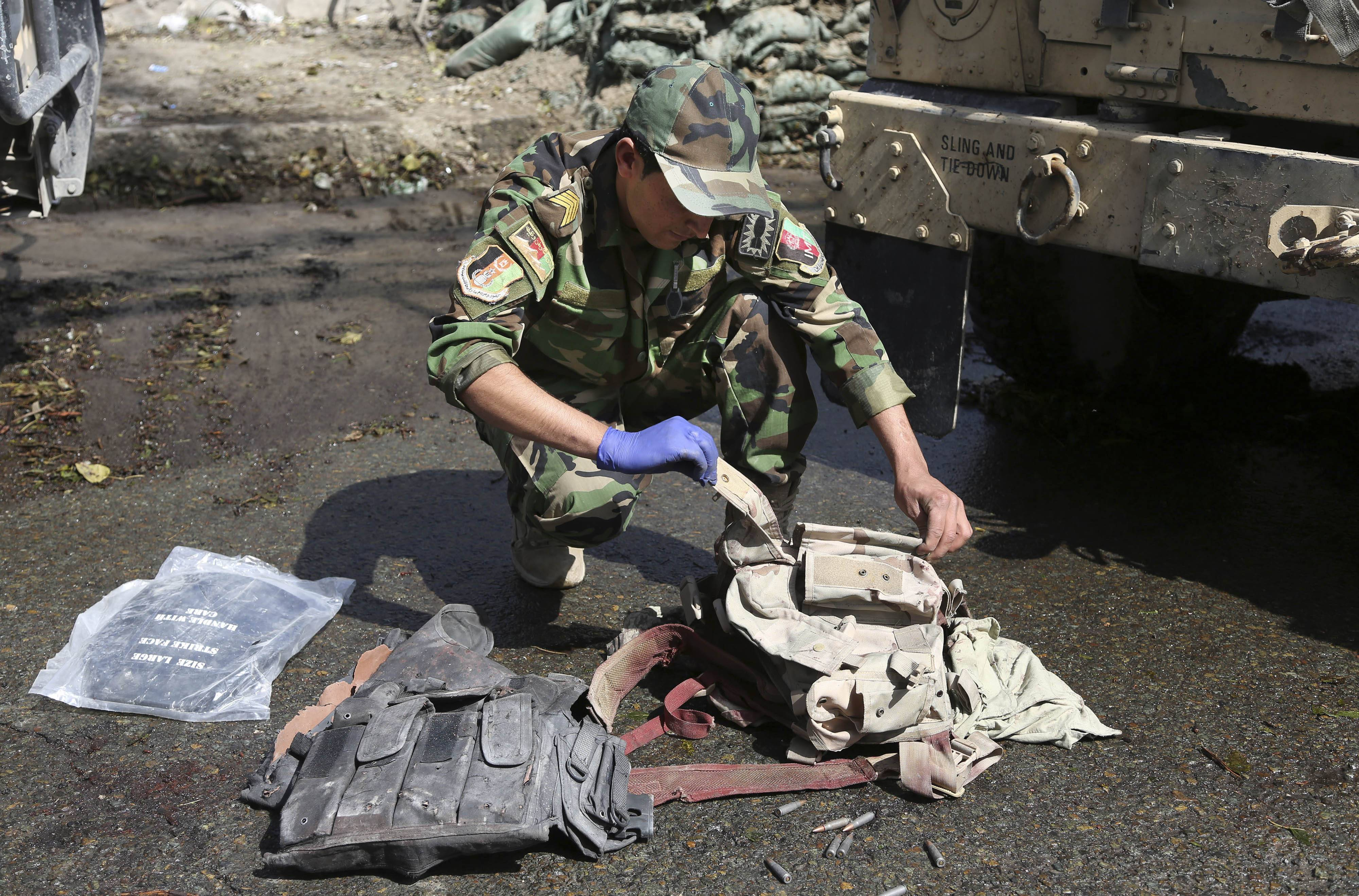 An Afghan Army soldier inspects bullet proof vests found after Taliban insurgents staged a multipronged attack on a police station in Jalalabad, eastern Afghanistan, Thursday, March 20, 2014. Taliban insurgents staged the attack, using a suicide bomber and gunmen to lay siege to the station, government officials said. Two remotely detonated bombs also exploded nearby.