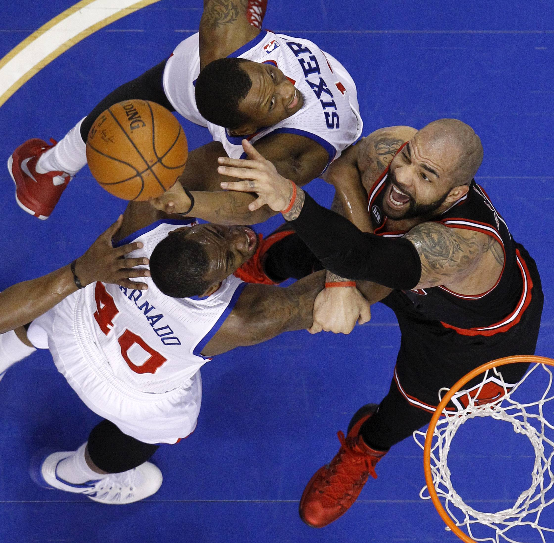 The Bulls' Carlos Boozer, right, battles for a rebound with the 76ers' James Nunnally, center, and Jarvis Varnado during Wednesday night's road game. The Bulls handed Philadelphia its 22nd straight loss.