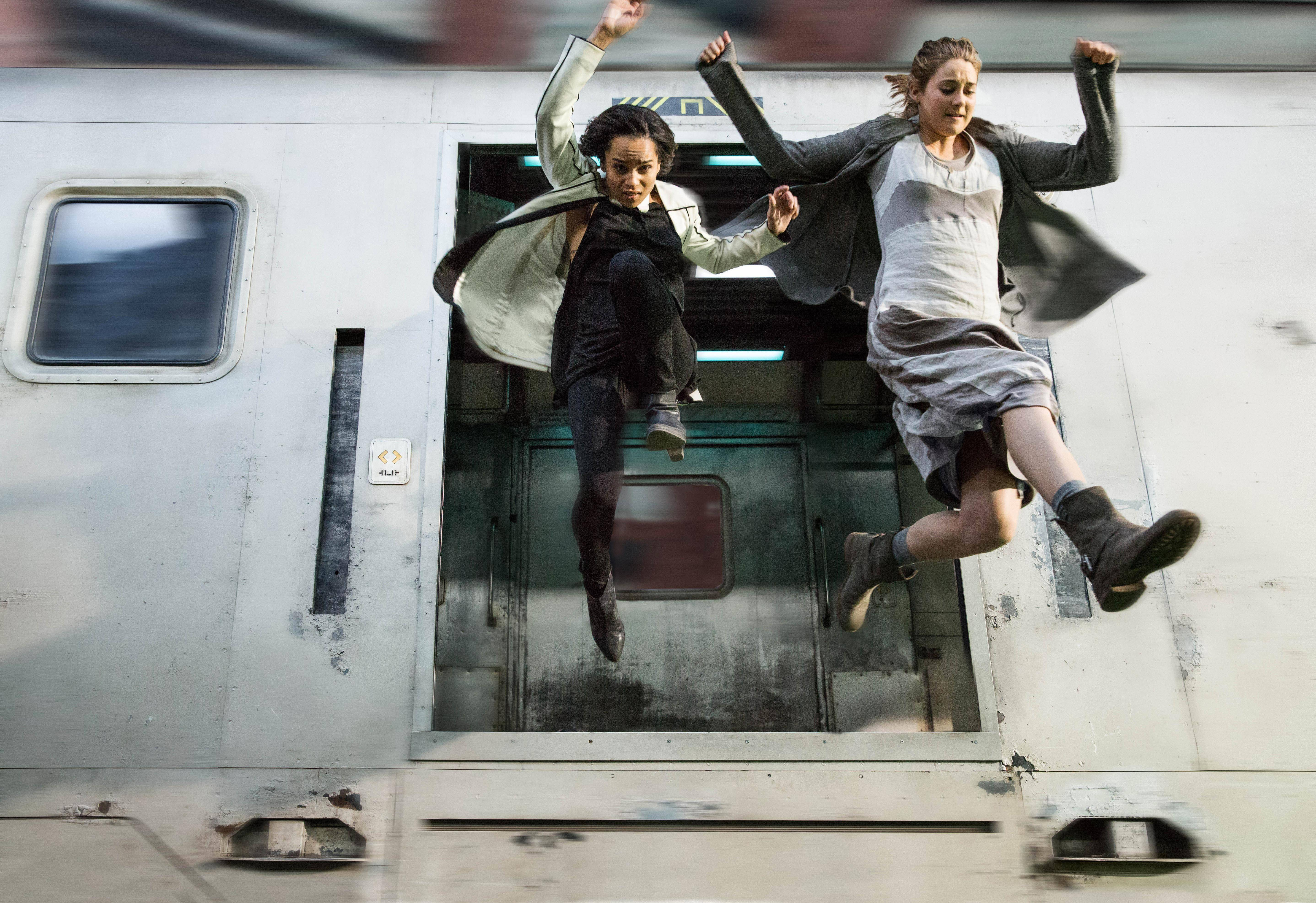 "Tris (Shailene Woodley), right, and her friend (Zoe Kravitz) leap for their lives from a Chicago el train in Neil Burger's ""Divergent,"" based on the novel by Barrington author Veronica Roth."