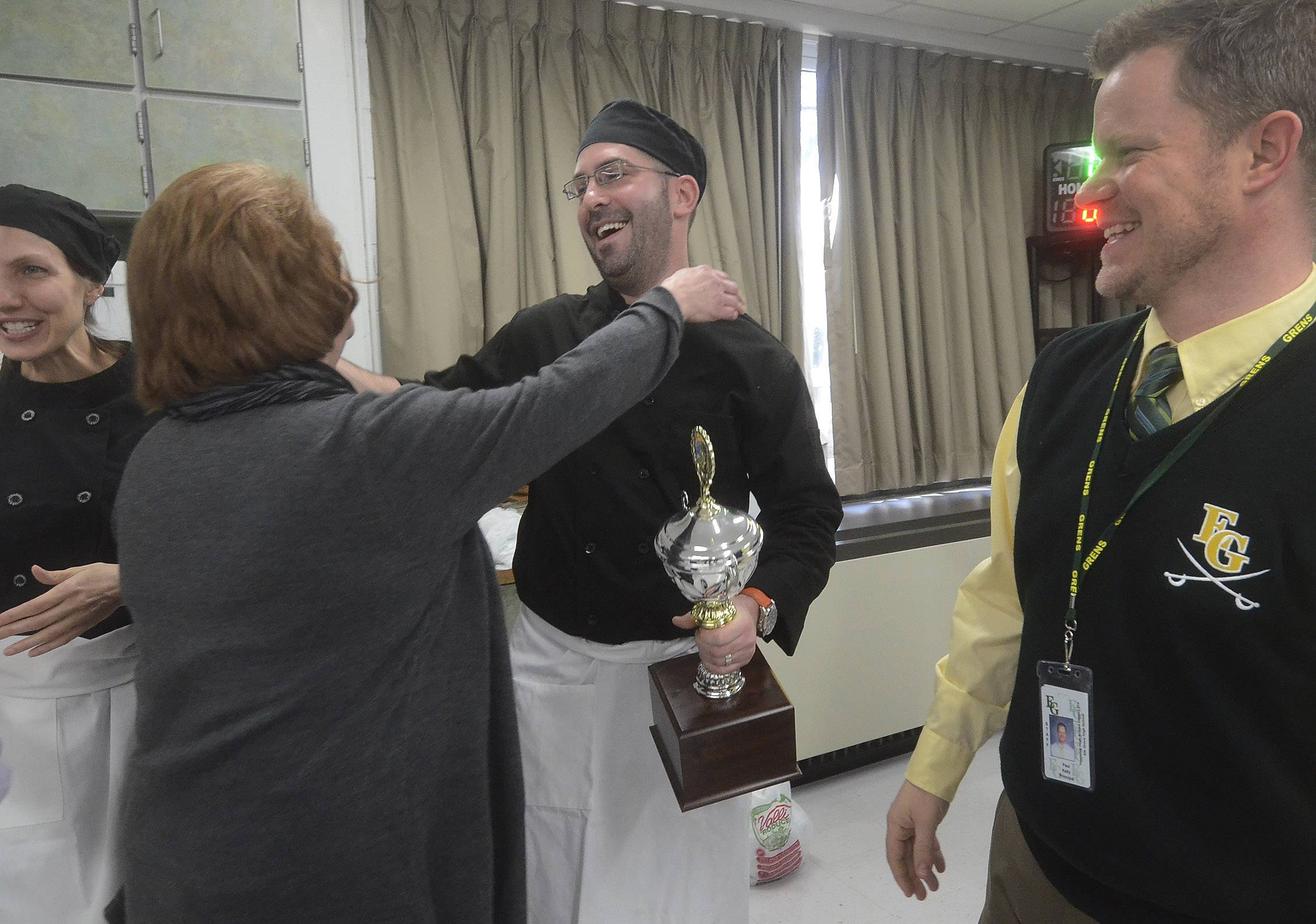 Elk Grove High School counselor Scott Deutsch is congratulated by two of the judges, cafeteria Manager Kathy Benn, left and Principal Paul Kelly, after his team won Elk Grove High School's ProStart vs. Faculty Cook-off.