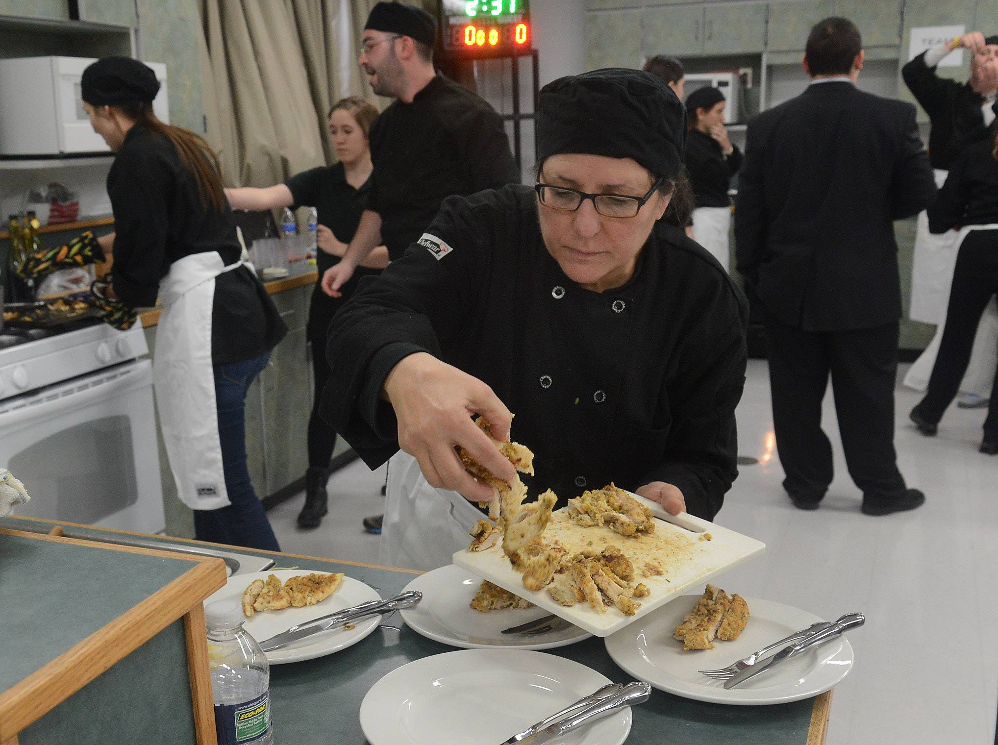 Social worker Sandy Bisinger works on Team Manga's sautéed breaded chicken breast during Elk Grove High School's ProStart vs. Faculty Cook-off.
