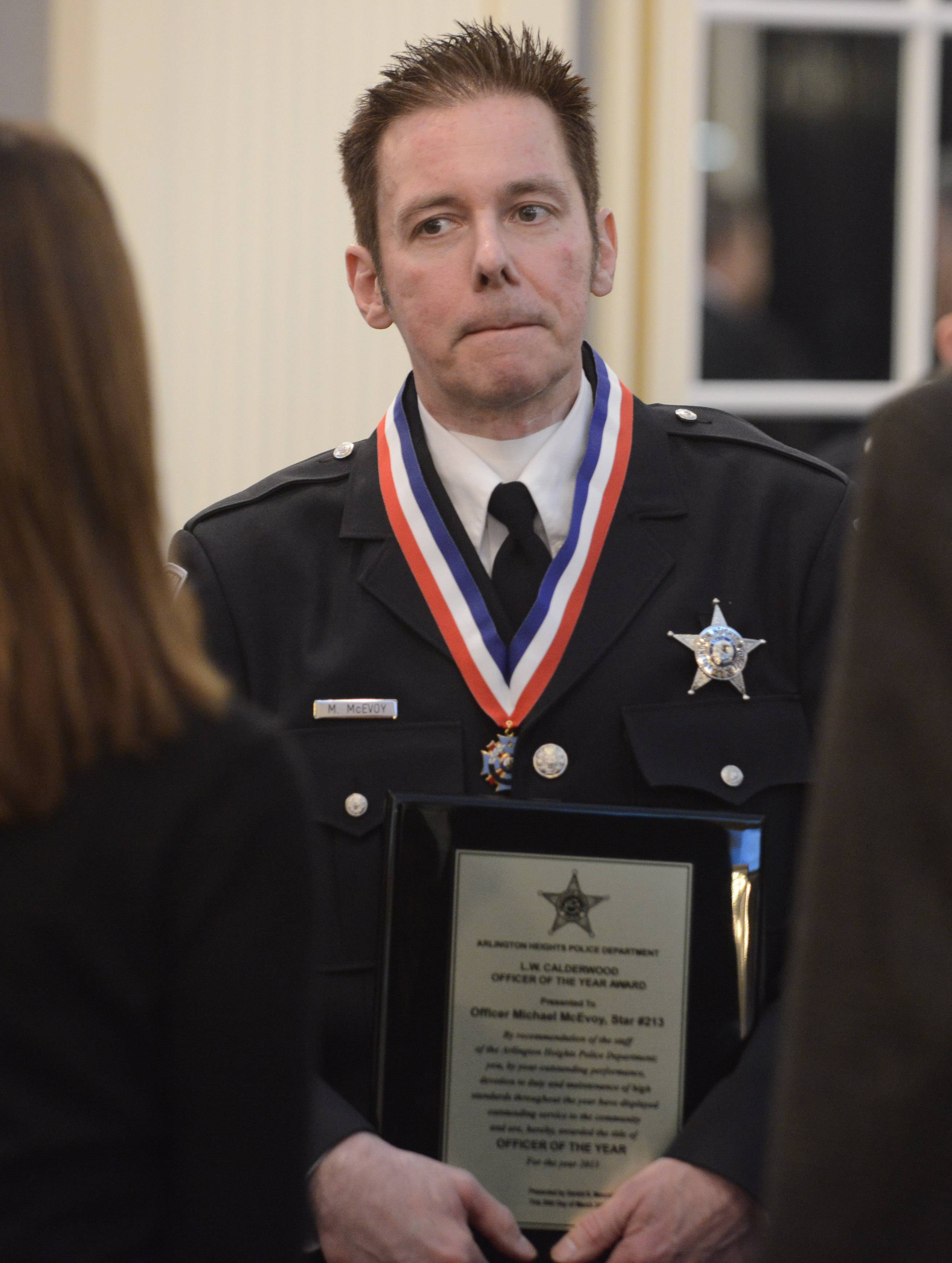 "Arlington Heights police officer Michael McEvoy holds the L.W. ""Bill"" Calderwood Officer of the Year award."