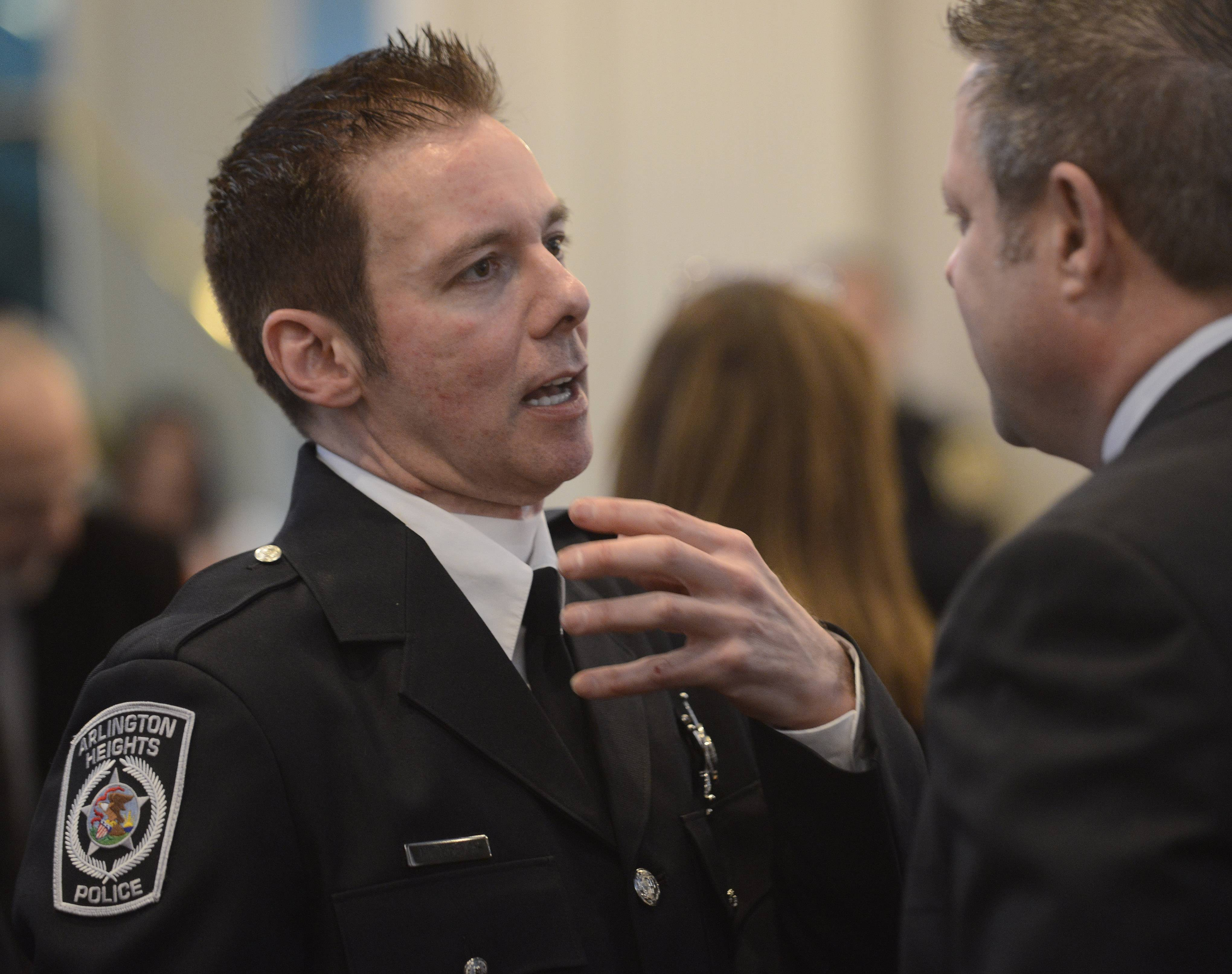 Arlington Heights police officer Michael McEvoy talks with Arlington Heights Trustee Tom Glasgow before the ceremony.