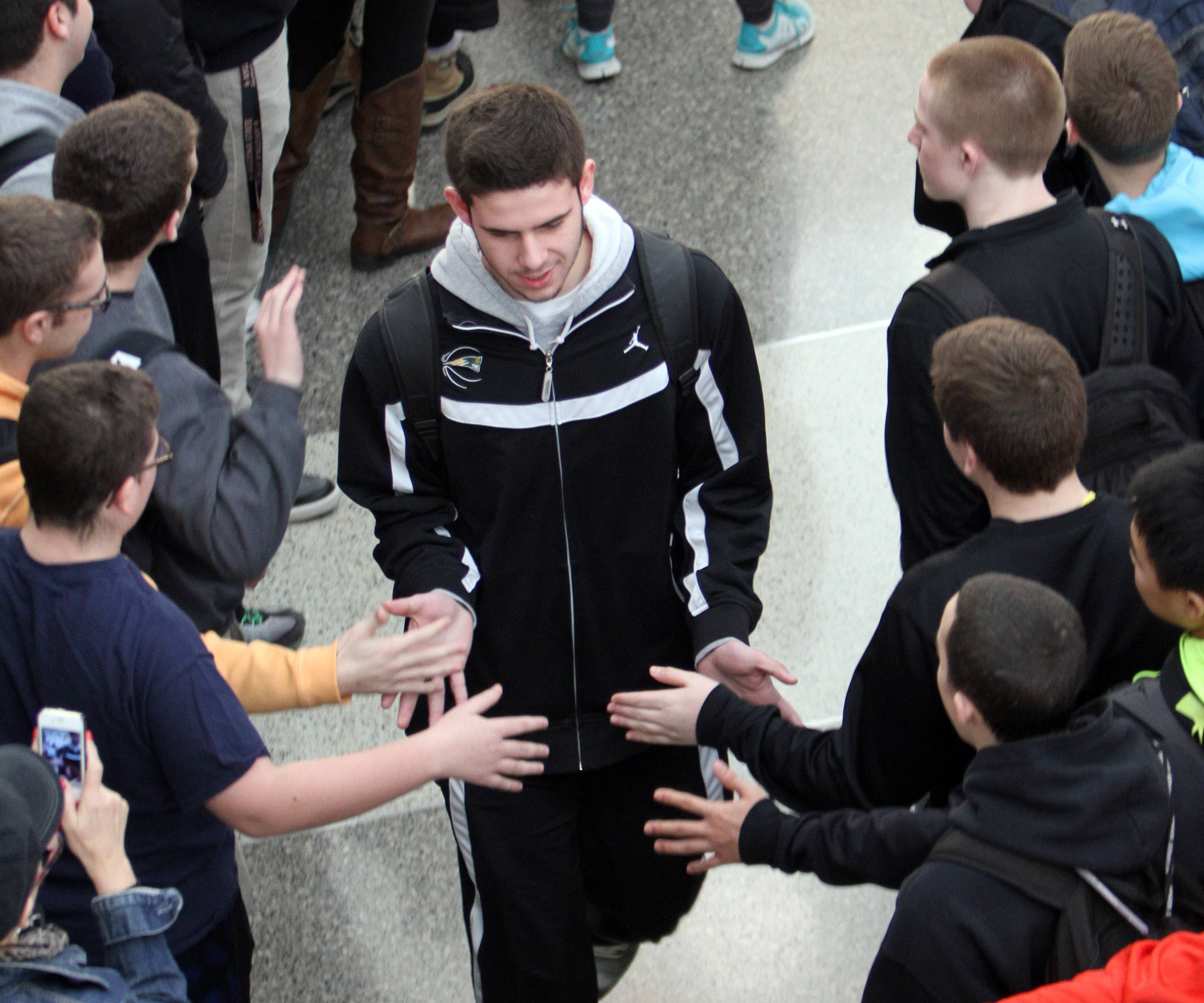 Parker Nichols high-fives students as the Stevenson High School boys basketball team gets a send off Thursday to the IHSA Class 4A state championships that start Friday in Peoria. Also honored were the school's debate and scholastic bowl teams, which compete for state championships this weekend.