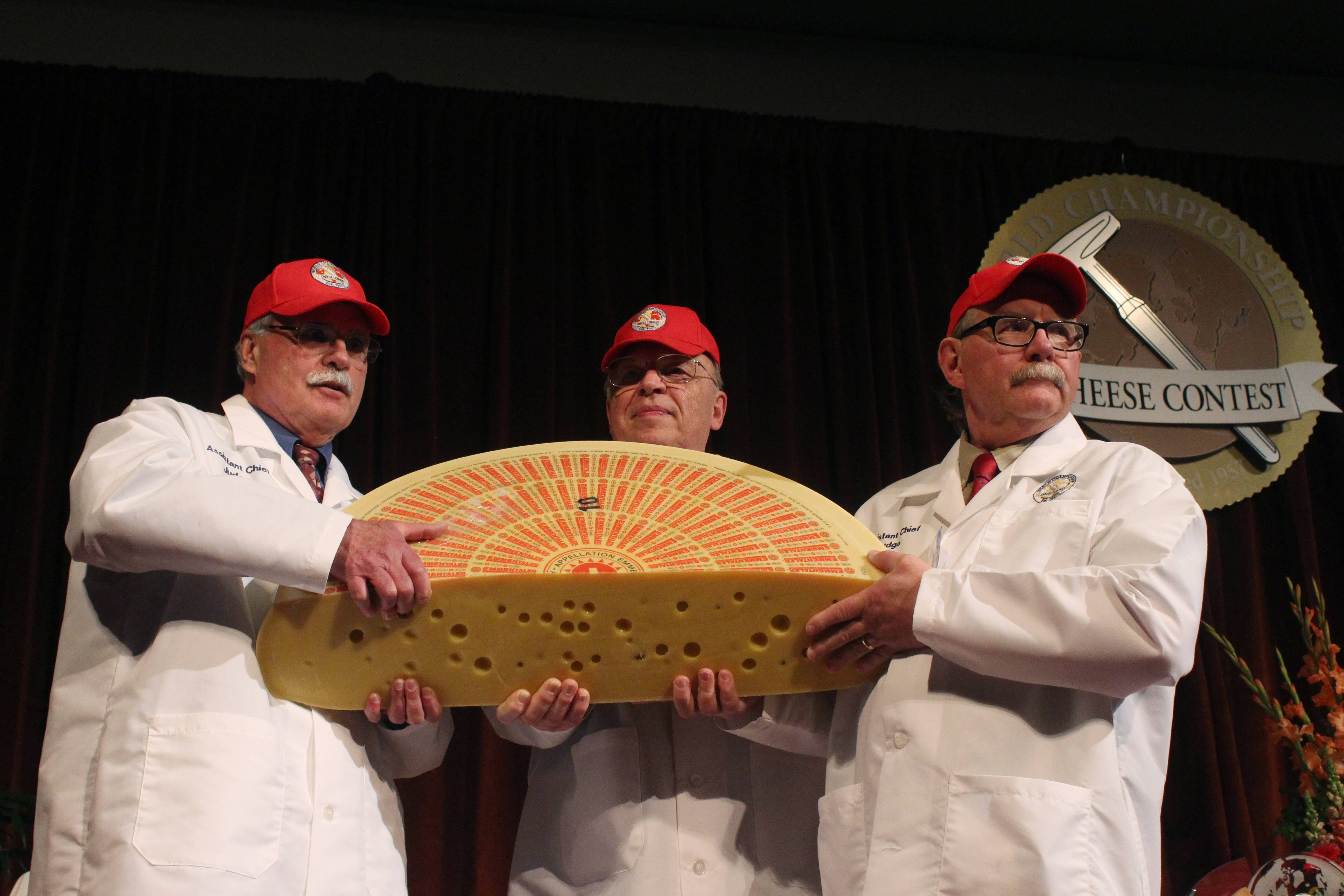 Three judges for the 2014 World Championship Cheese Contest hold the champion, a Swiss Emmentaler.