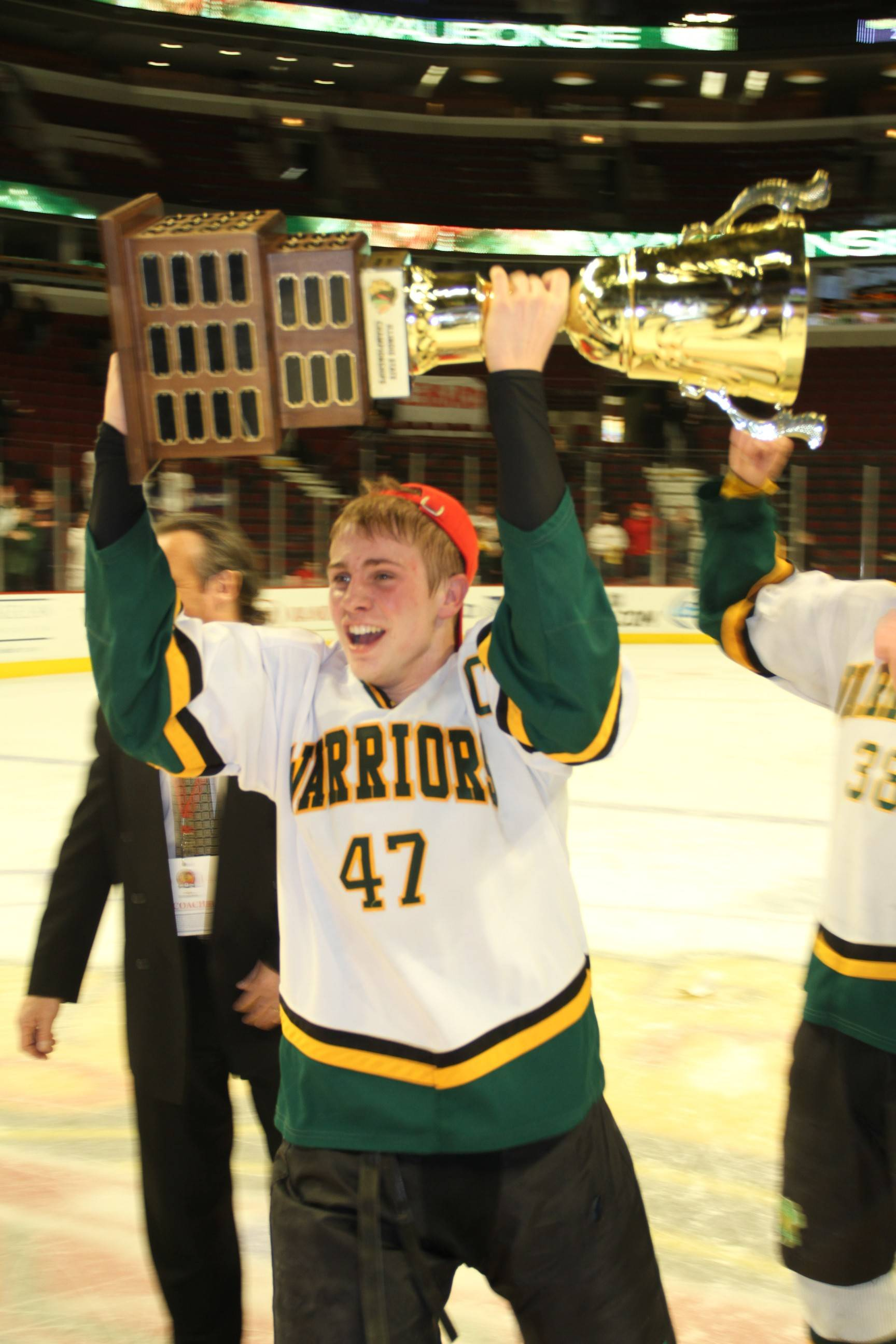 Waubonsie Valley's Ben Vietri skates with the Combined Division championship trophy after a 3-0 victory over Glenbard on Thursday at the United Center.