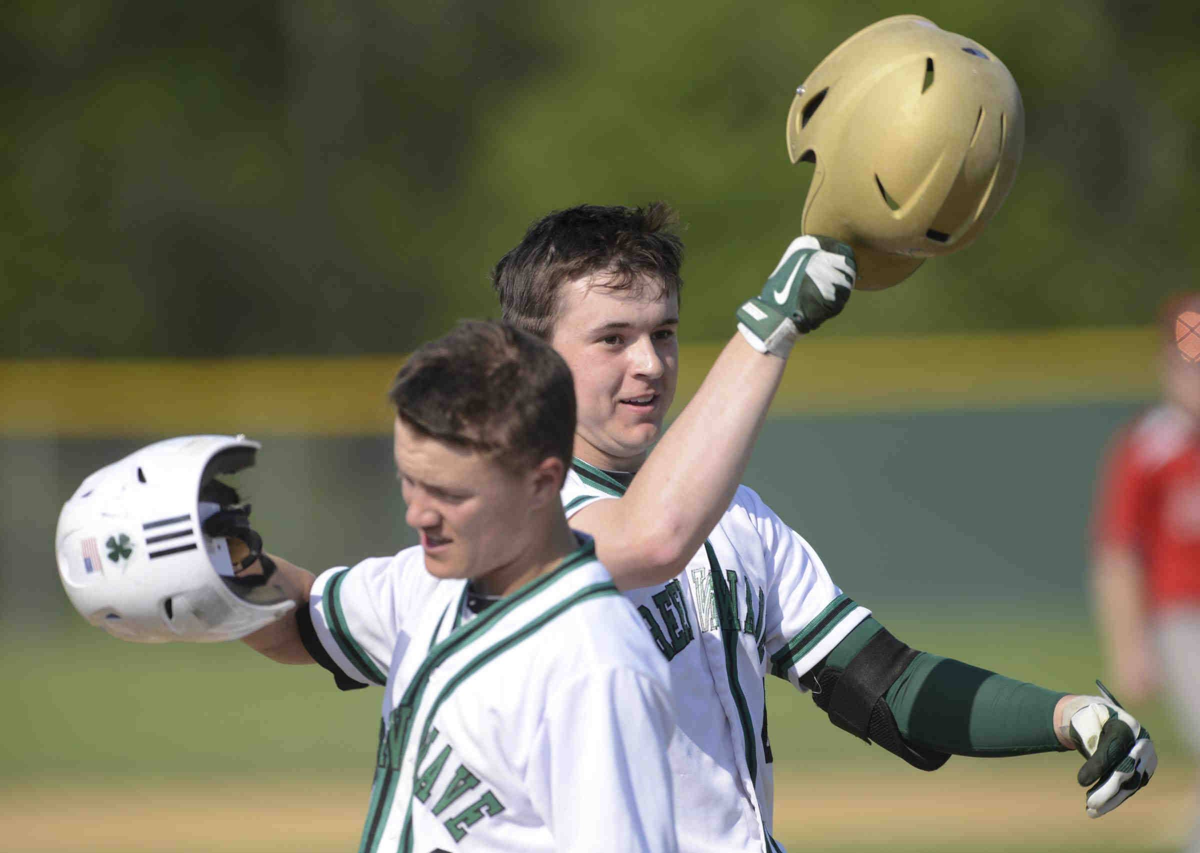 St. Edward's Jack Tierney taps his helmet with teammate Michael Castoro during a regional game against Aurora Christian last year.