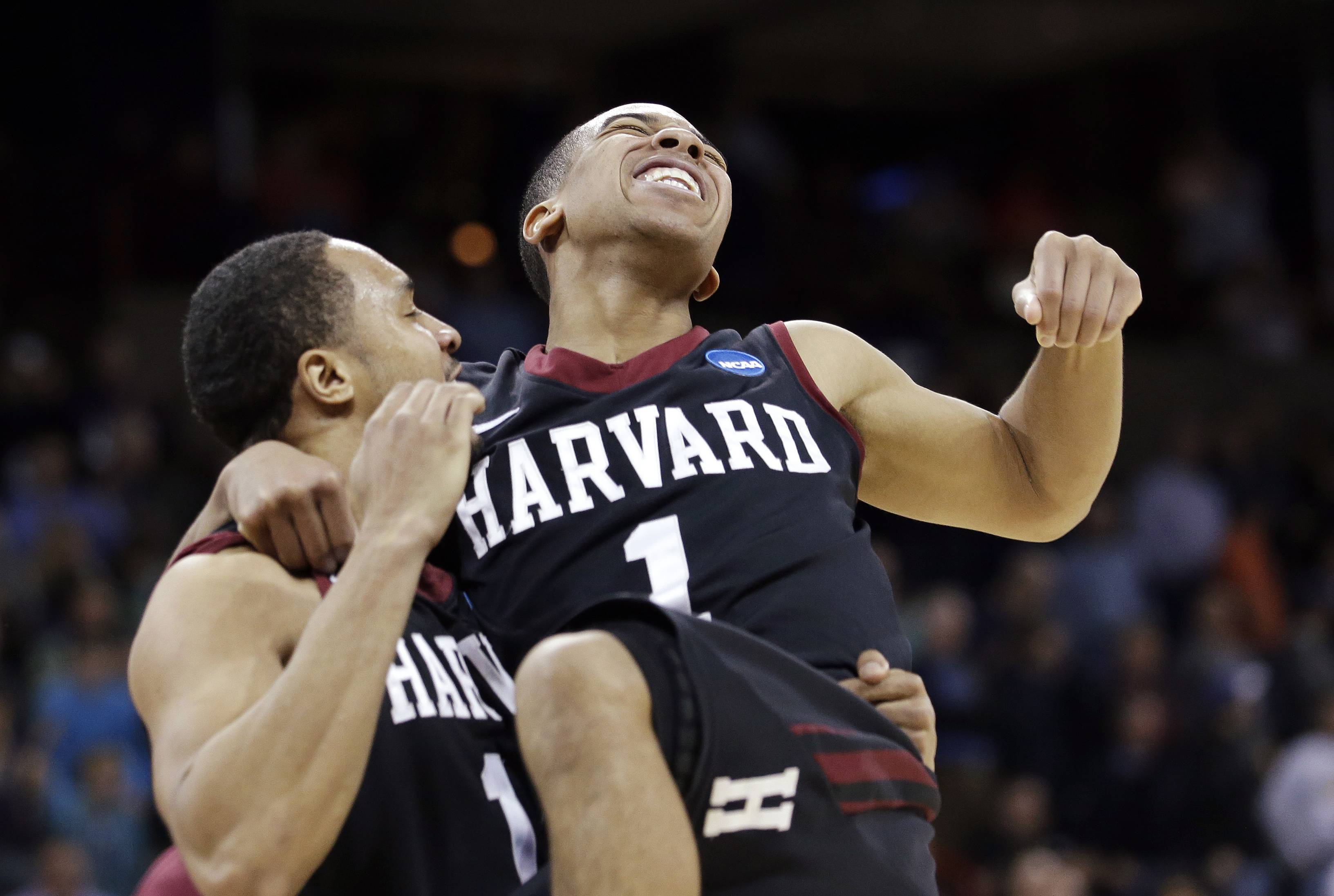 Harvard's Siyani Chambers, right, leaps into the arms of teammate Brandyn Curry after the team beat Cincinnati in the second round of the NCAA college basketball tournament in Spokane, Wash., Thursday, March 20, 2014. Harvard won 61-57.