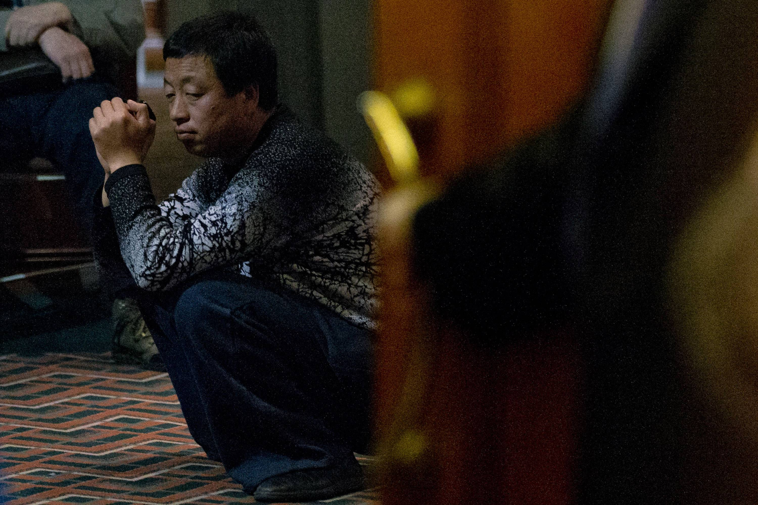 One of the relatives of Chinese passengers aboard missing Malaysia Airlines Flight MH370 waits to attend a briefing meeting with Malaysian officials in a hotel ballroom in Beijing, China, Friday, March 21, 2014.