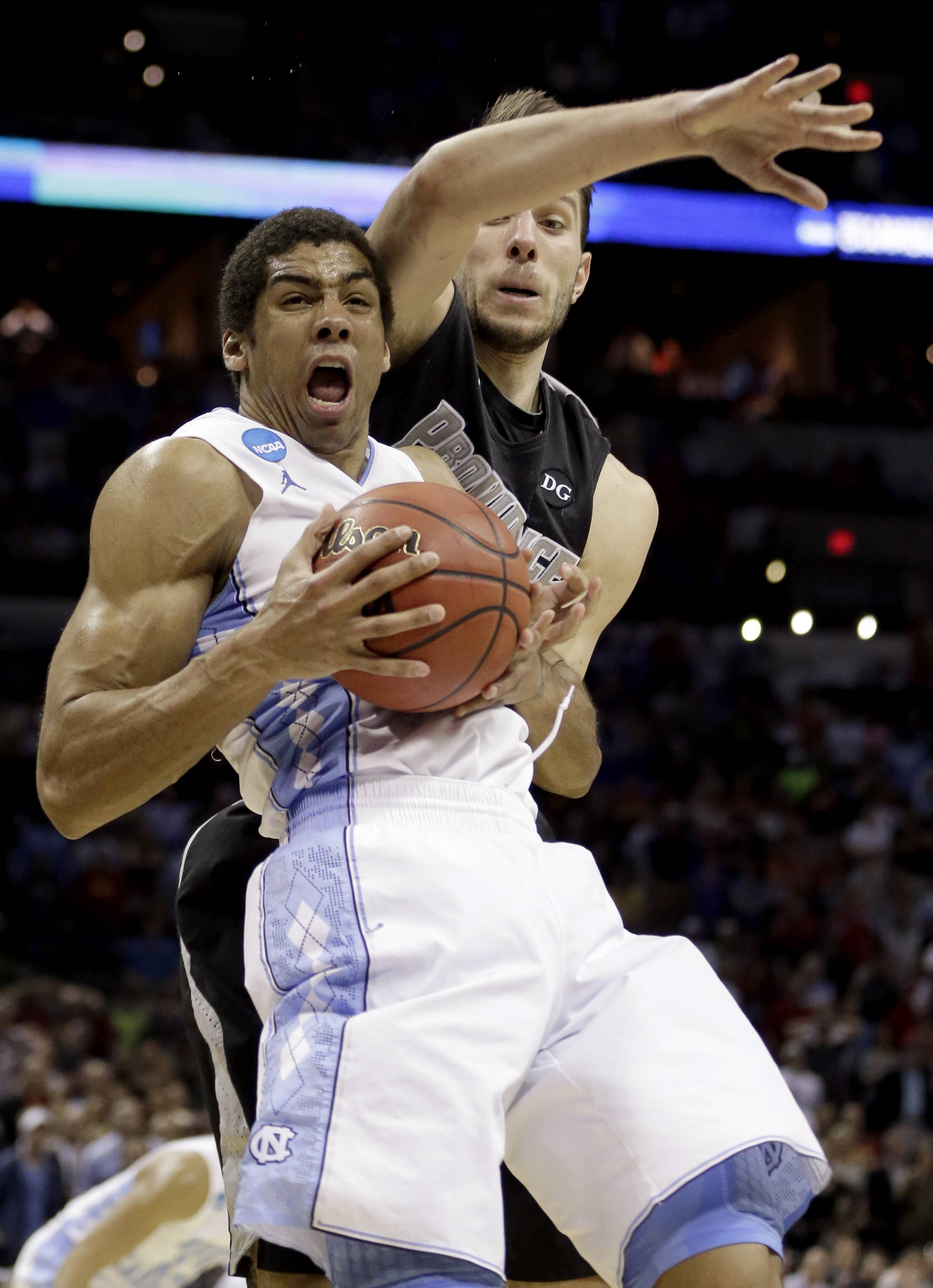 North Carolina's James Michael McAdoo, left, is fouled by Providence's Carson Desrosiers during the closing seconds an NCAA tournament game Friday in San Antonio. McAdoo's free throws lifted North Carolina to a 79-77 win.