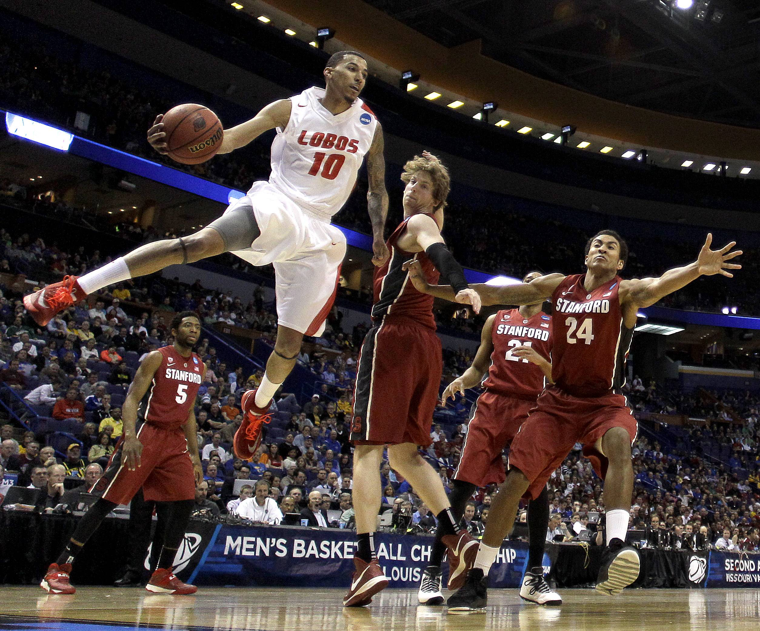 New Mexico's Kendall Williams (10) passes around Stanford's John Gage during the second half of a second-round game in the NCAA college basketball tournament, Friday, March 21, 2014, in St. Louis. Stanford won the game 58-53. (AP Photo/Charlie Riedel)