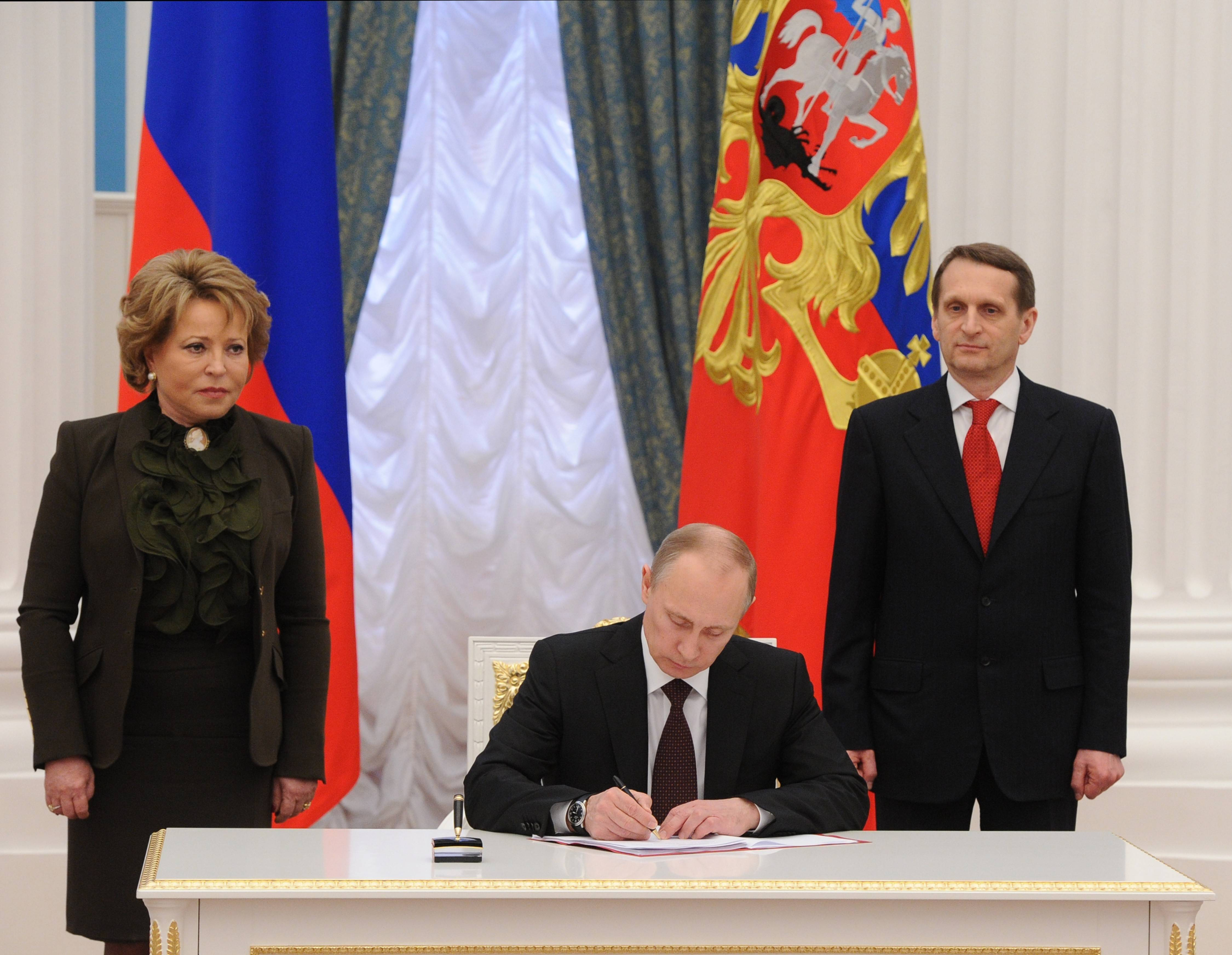 Russian President Vladimir Putin, flanked by Upper House Speaker Valentina Matviyenko, left, and Lower House Speaker Sergei Naryshkin, signs bills Friday making Crimea part of Russia in the Kremlin in Moscow.
