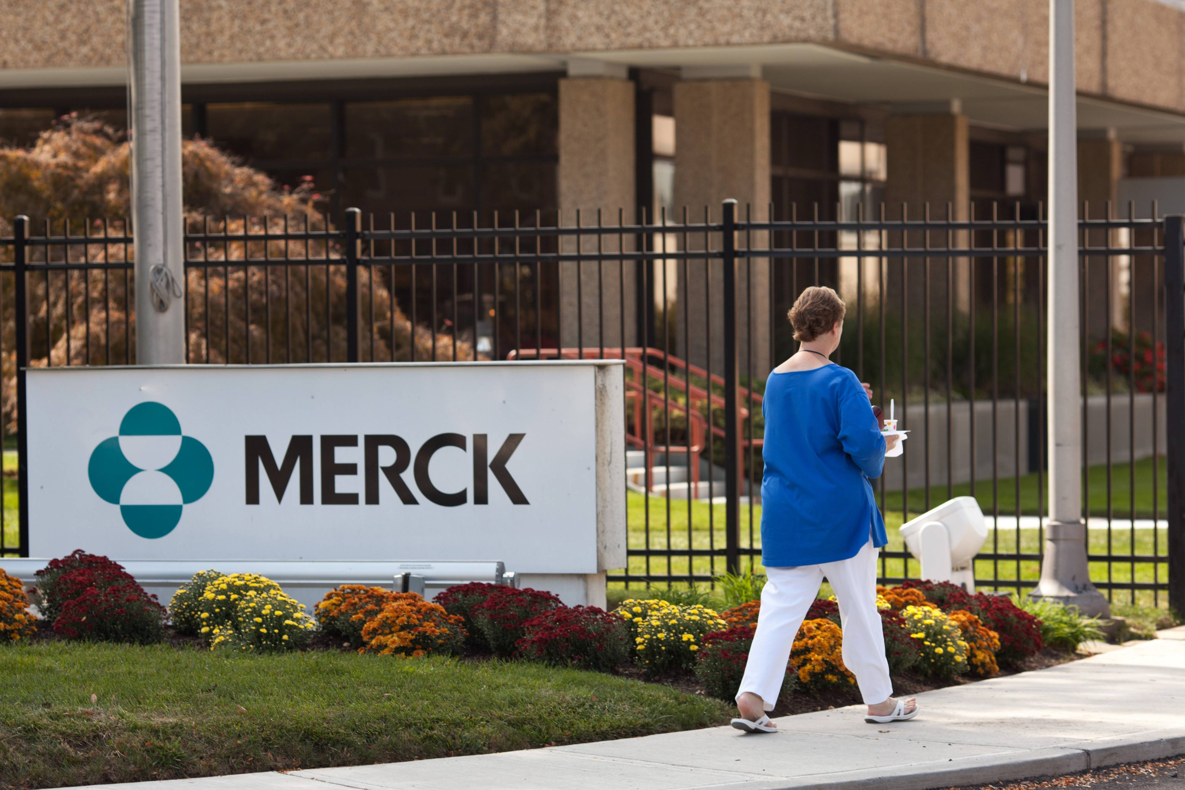 A pedestrian walks outside a Merck & Co. facility in Summit, New Jersey. The second-biggest U.S. drugmaker by sales will lay off 8,500 workers and revamp its research and development after seeing new medicines delayed by U.S. regulators.