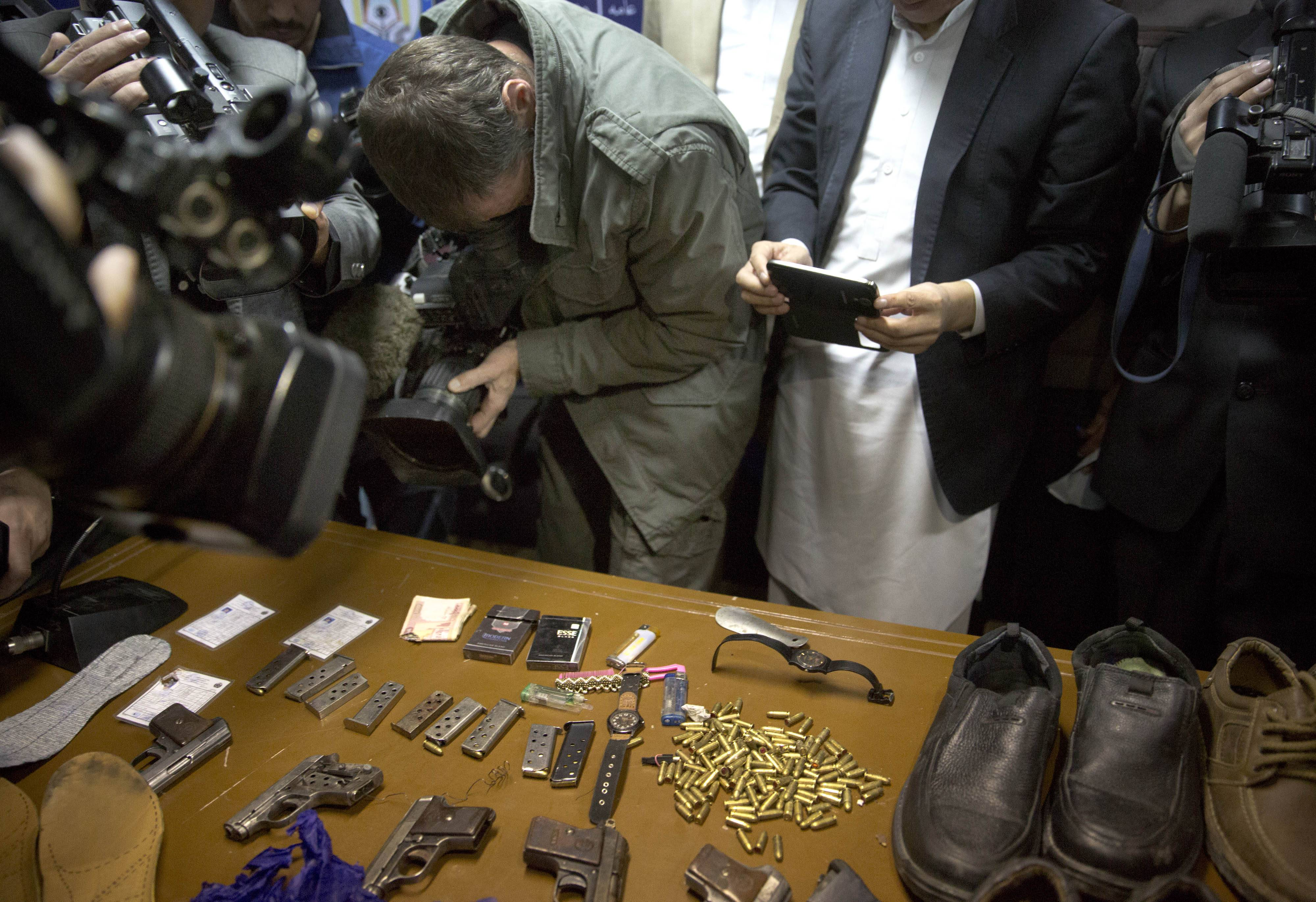 Journalists film some of the weapons and belongings that where used by gunmen during an attack on the Serena hotel  Thursday, and displayed by Afghanistan's intelligence service, during a press conference at the interior ministry in Kabul, Afghanistan, Friday, March 21, 2014.  Four men hiding guns in their shoes attacked the hotel in Kabul opening fire in a restaurant killing at least nine people, including four foreigners, officials said. Authorities appeared stunned that the militants had managed to get through the tight security at the Serena hotel -- considered one of the safest places to stay in Kabul.