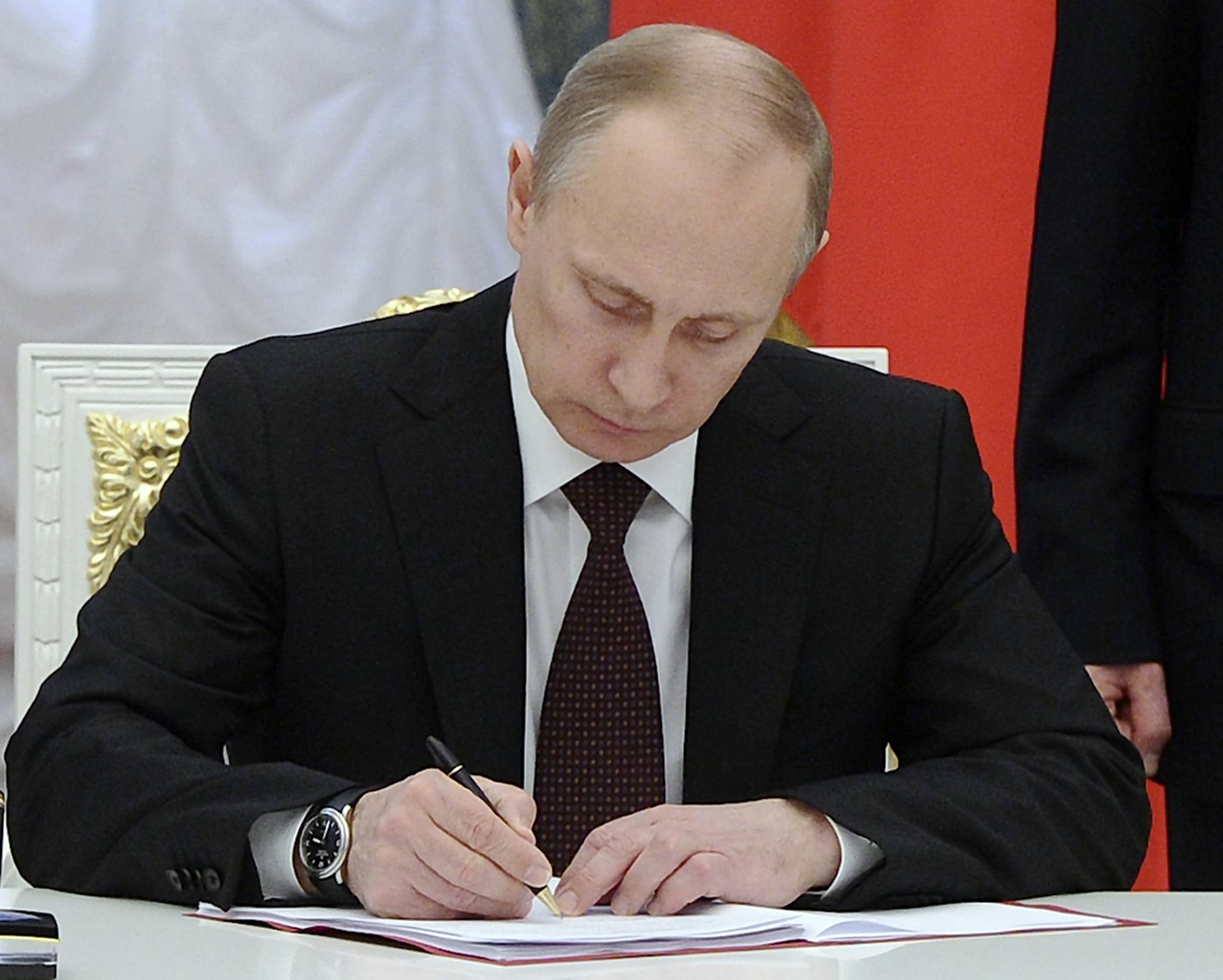 Russian President Vladimir Putin signs bills making Crimea part of Russia in the Kremlin in Moscow, Friday, March 21, 2014. President Vladimir Putin completed the annexation of Crimea on Friday, signing the peninsula into Russia at nearly the same time his Ukrainian counterpart sealed a deal pulling his country closer into Europe's orbit.