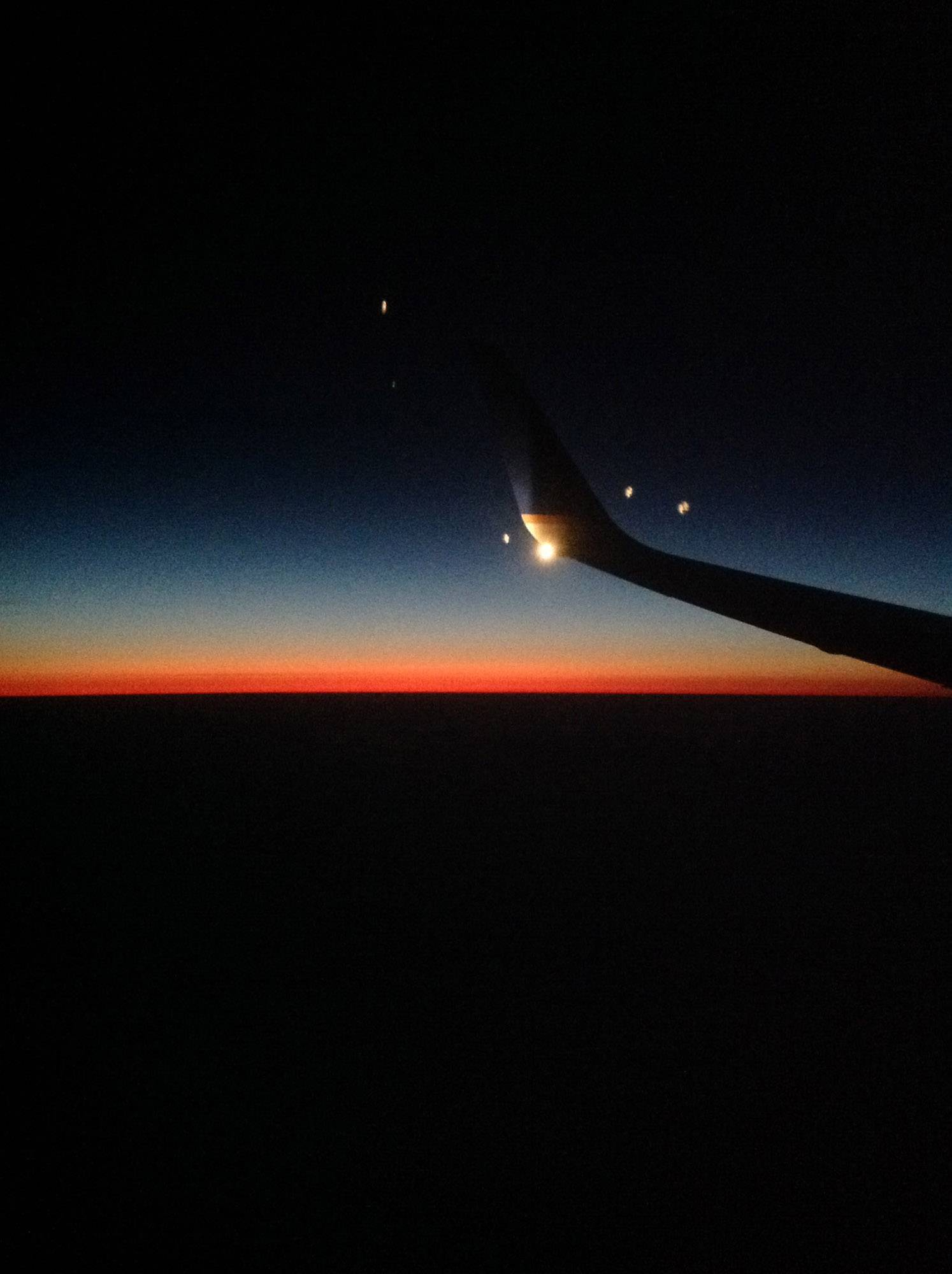 The lights from the wing on an airplane shine against the sunset during a flight home from Puerto Villarta on March 8.