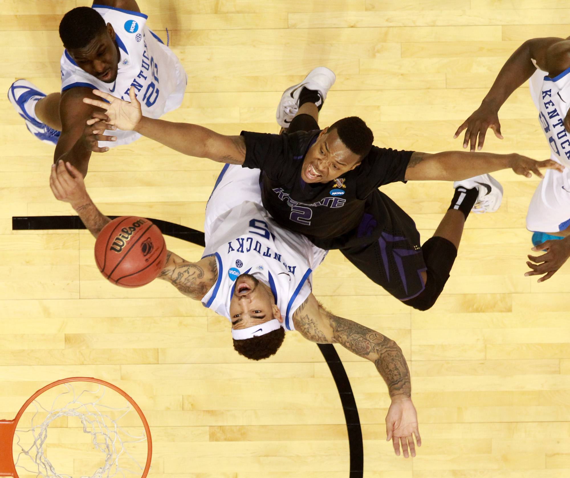 Kansas State guard Marcus Foster, right, has his shot contested by Kentucky forward Willie Cauley-Stein, lower, and forward Alex Poythress during an NCAA tournament game Friday at the Scottrade Center in St. Louis.