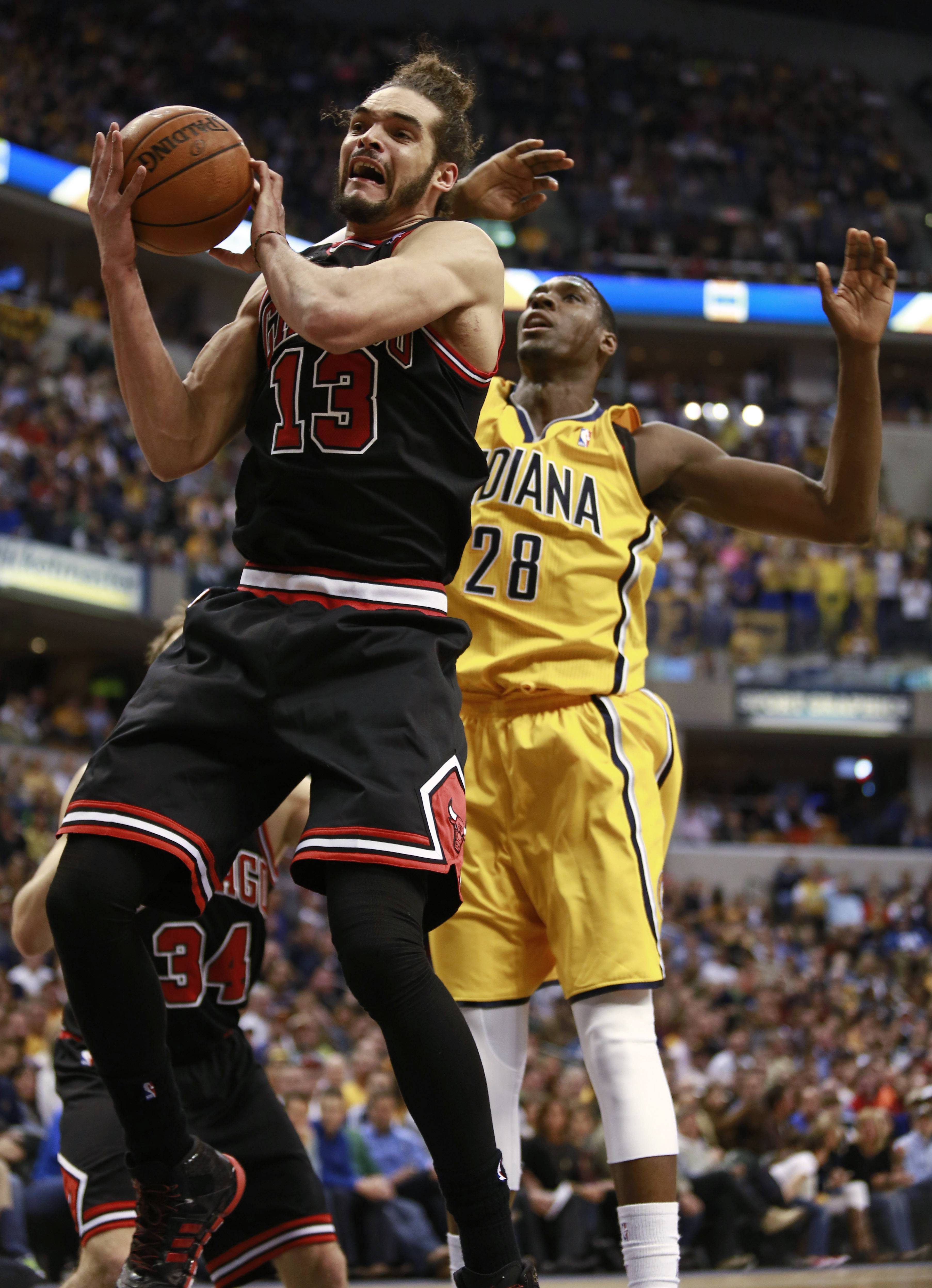 Chicago Bulls center Joakim Noah, left, grabs a rebound in front of Indiana Pacers center Ian Mahinmi in the second half of an NBA basketball game in Indianapolis, Friday, March 21, 2014. Indiana won 91-79.