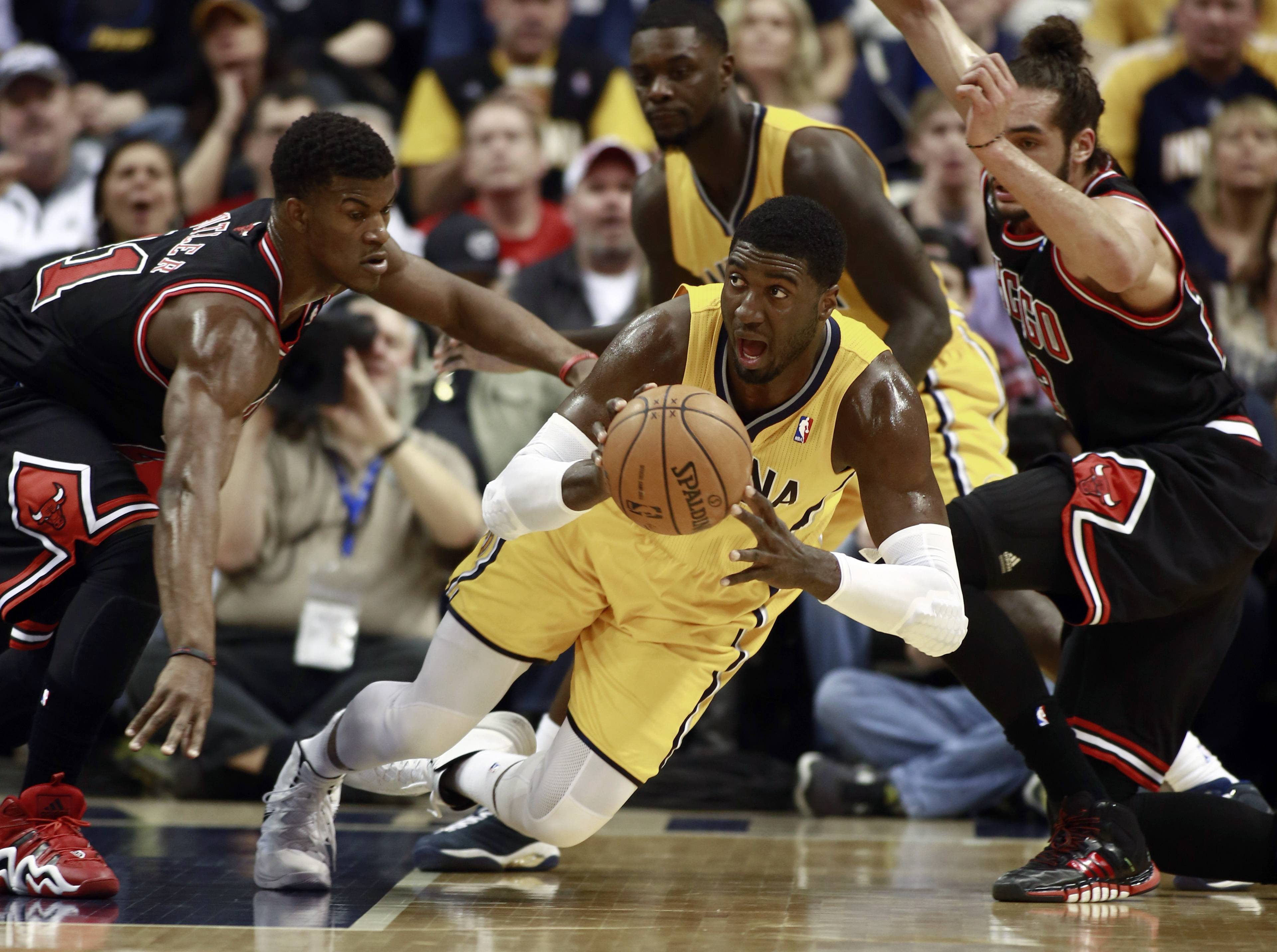 Indiana Pacers center Roy Hibbert passes the basketball while falling as Chicago Bulls guard Jimmy Butler, left, and center Joakim Noah, right, defend during the first half of an NBA basketball game in Indianapolis, Friday, March 21, 2014.