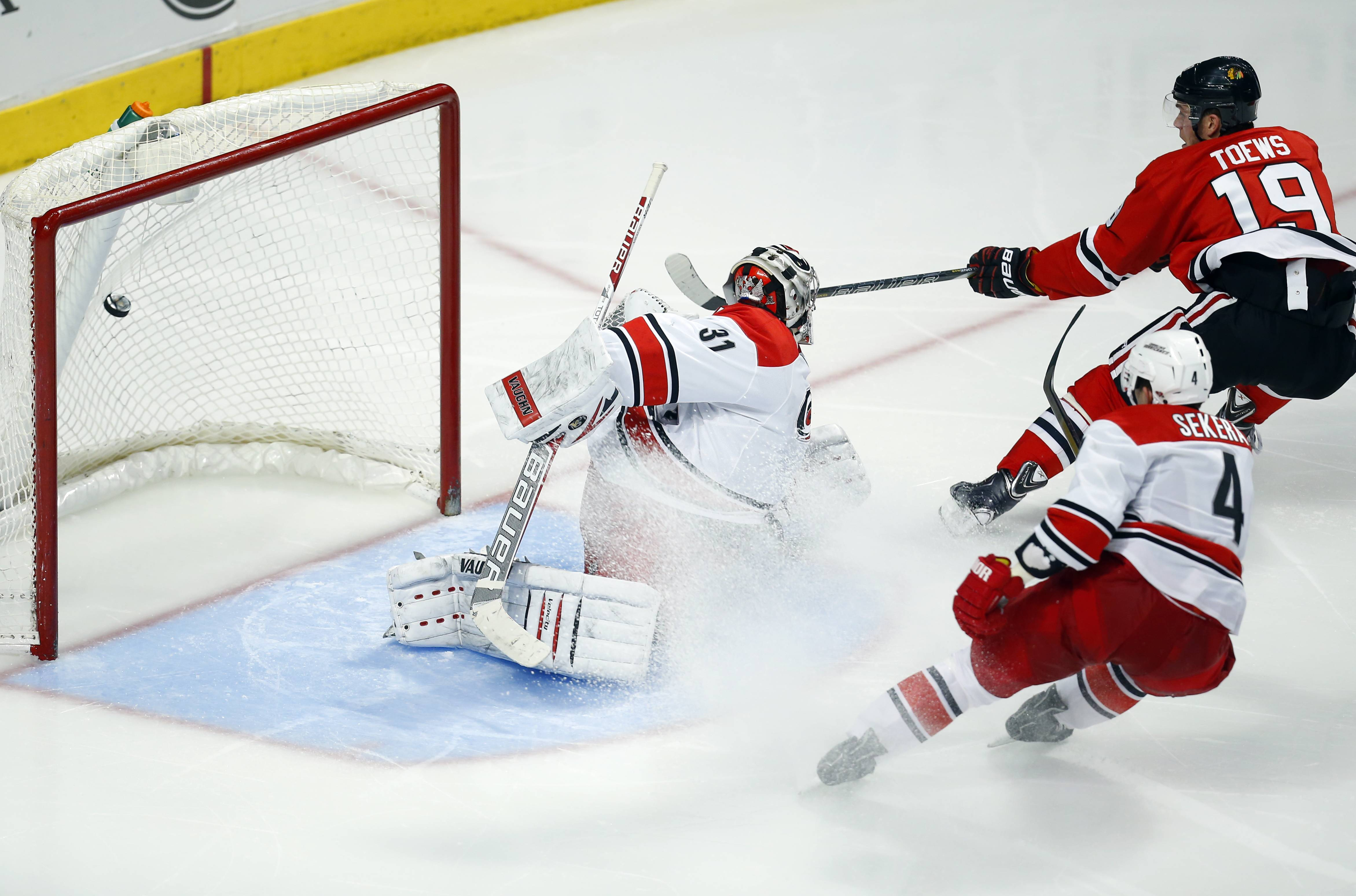 Chicago Blackhawks center Jonathan Toews (19) gets the puck past Carolina Hurricanes goalie Anton Khudobin (31) for a goal as Hurricanes defenseman Andrej Sekera (4) trails the play during the third period of an NHL hockey game in Chicago, Friday, March 21, 2014. The Blackhawks won 3-2.