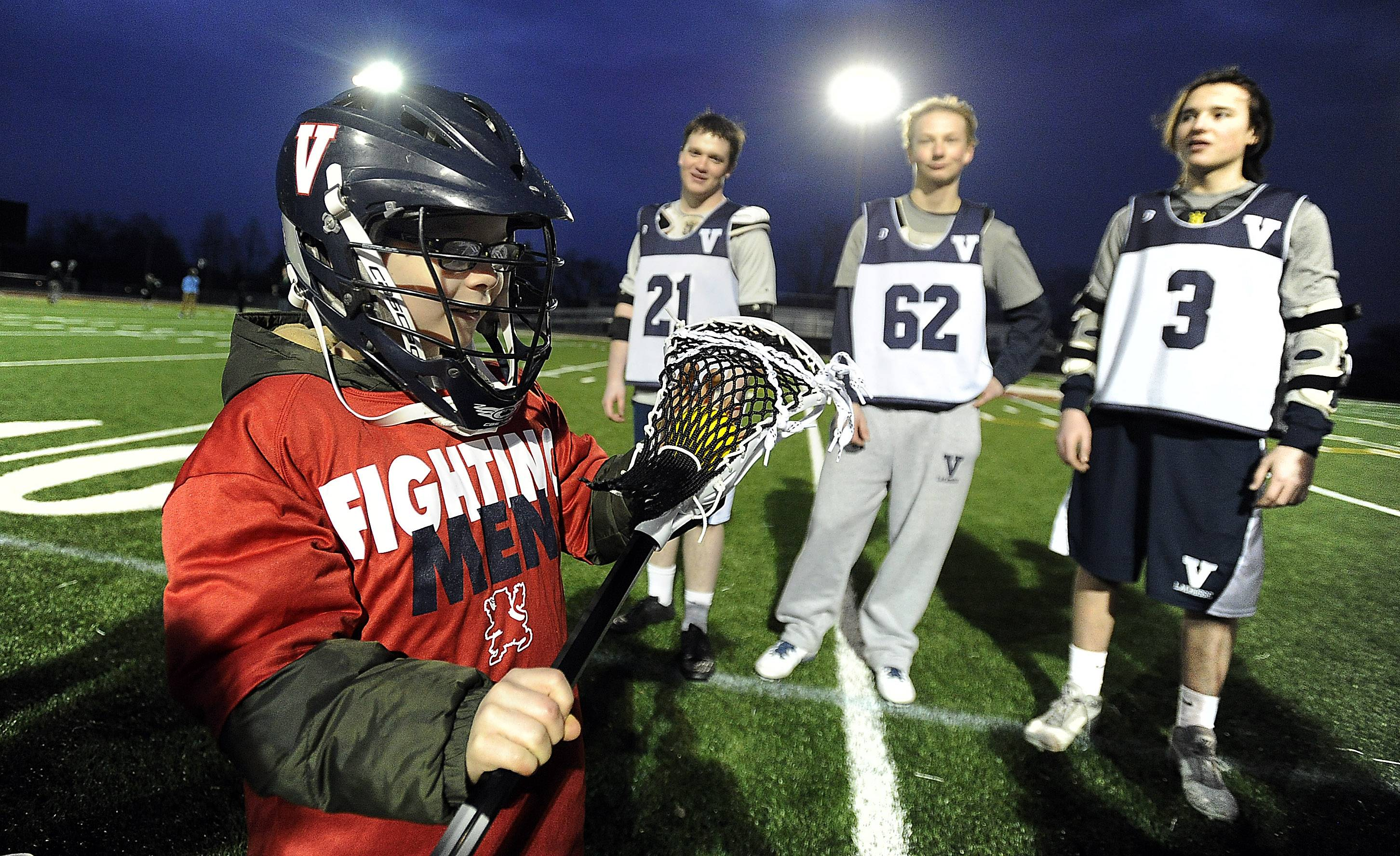 The St. Viator boys lacrosse team honored 8-year-old Dylan Full, who has been battling cancer, as part of Friday's game against Marian Catholic at Forest View Educational Center. Here, Lions players Kevin McMahon, Peter Schmidt and Brian Julius watch as Full looks over his new equipment.