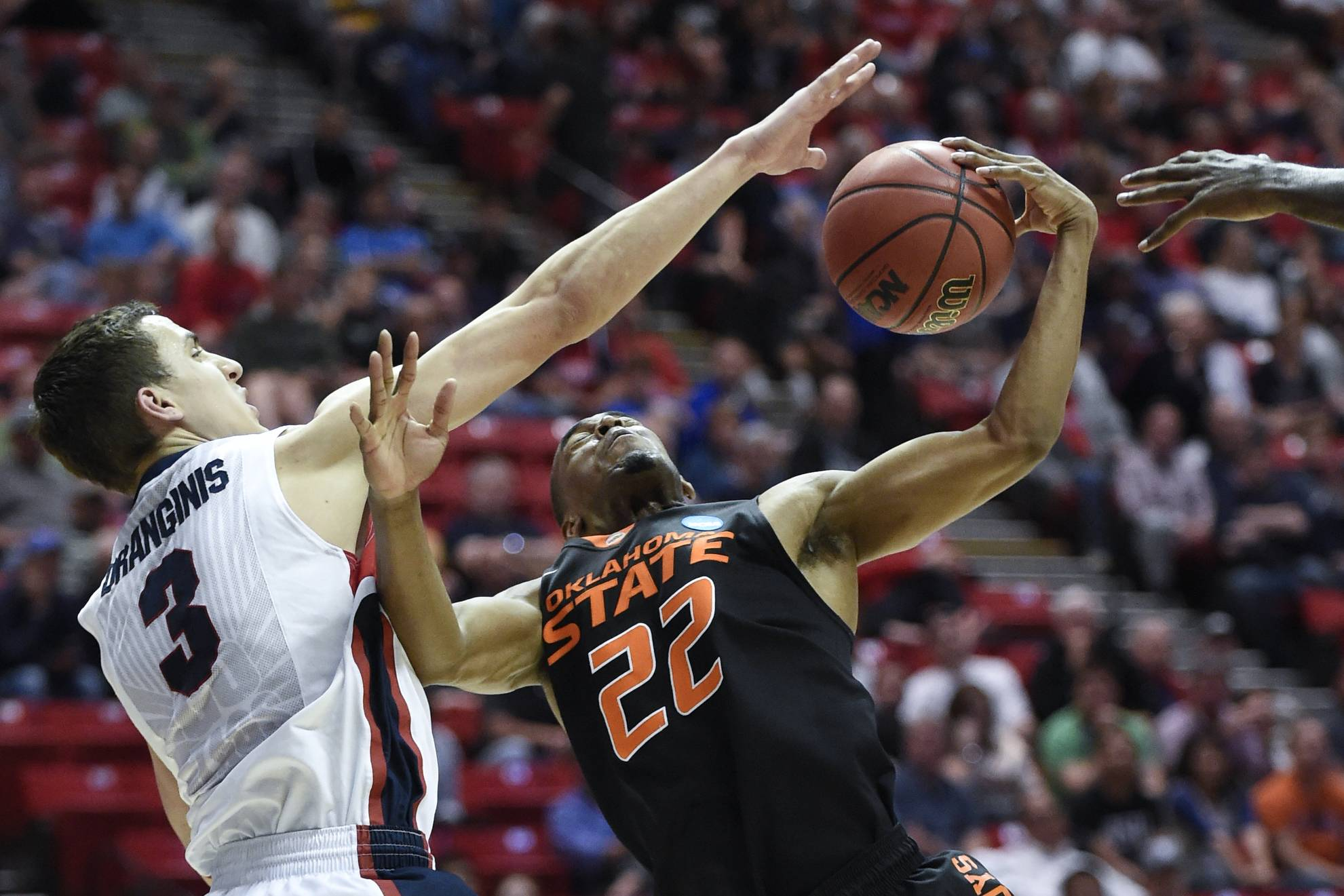 Gonzaga guard Kyle Dranginis, left, blocks a shot by Oklahoma State guard Markel Brown during the second half in a second-round game in the NCAA men's college basketball tournament Friday, March 21, 2014, in San Diego. Gonzaga won 85-77.