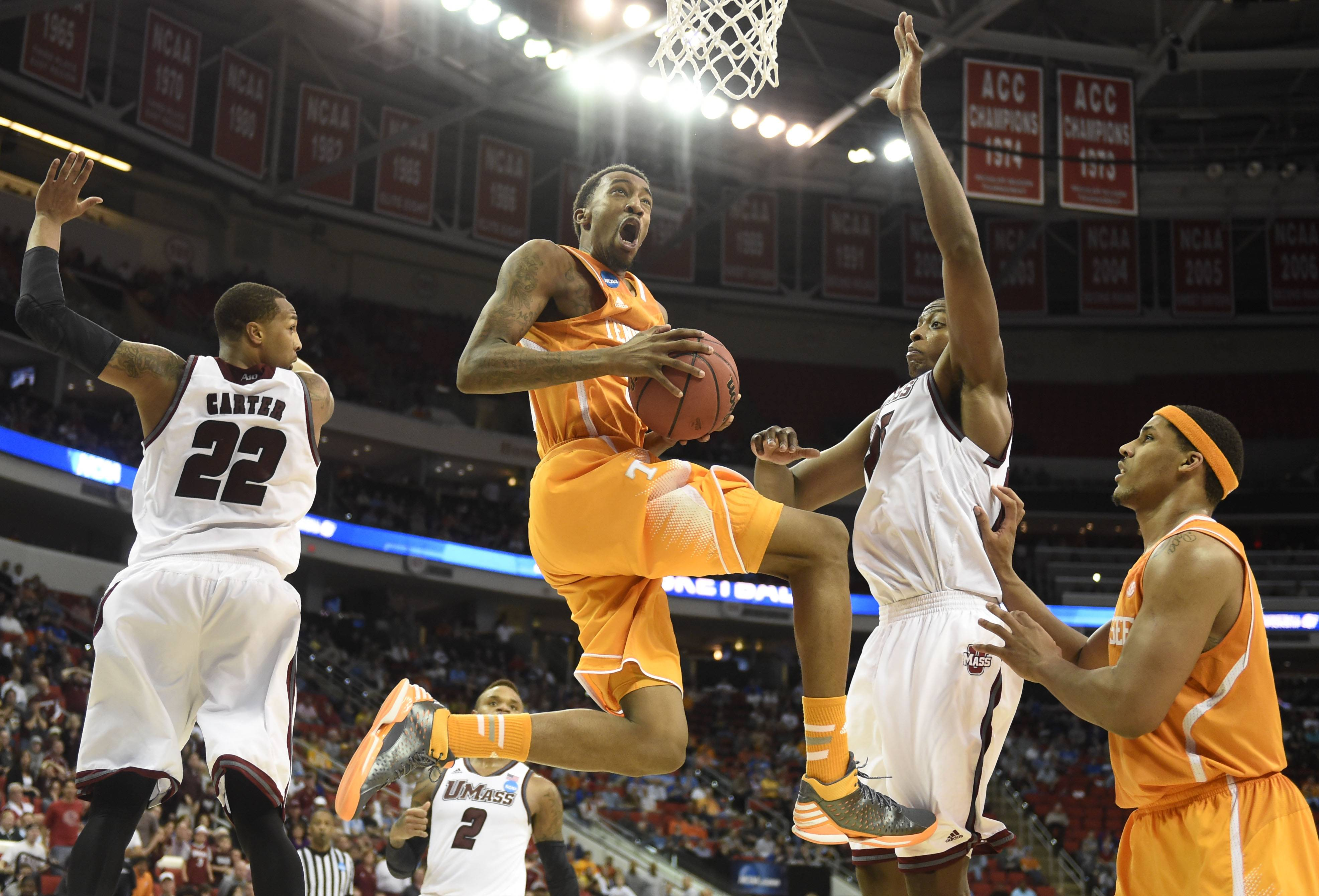Tennessee guard Jordan McRae (52), center, gets to the hoop in between Massachusetts forward Sampson Carter (22) and Massachusetts center Cady Lalanne (25), while Tennessee forward Jarnell Stokes, right, looks on during the second half of an NCAA college basketball tournament game at the PNC Arena in Raleigh, N.C. on Friday, March 21, 2014. Tennessee won 86-67.