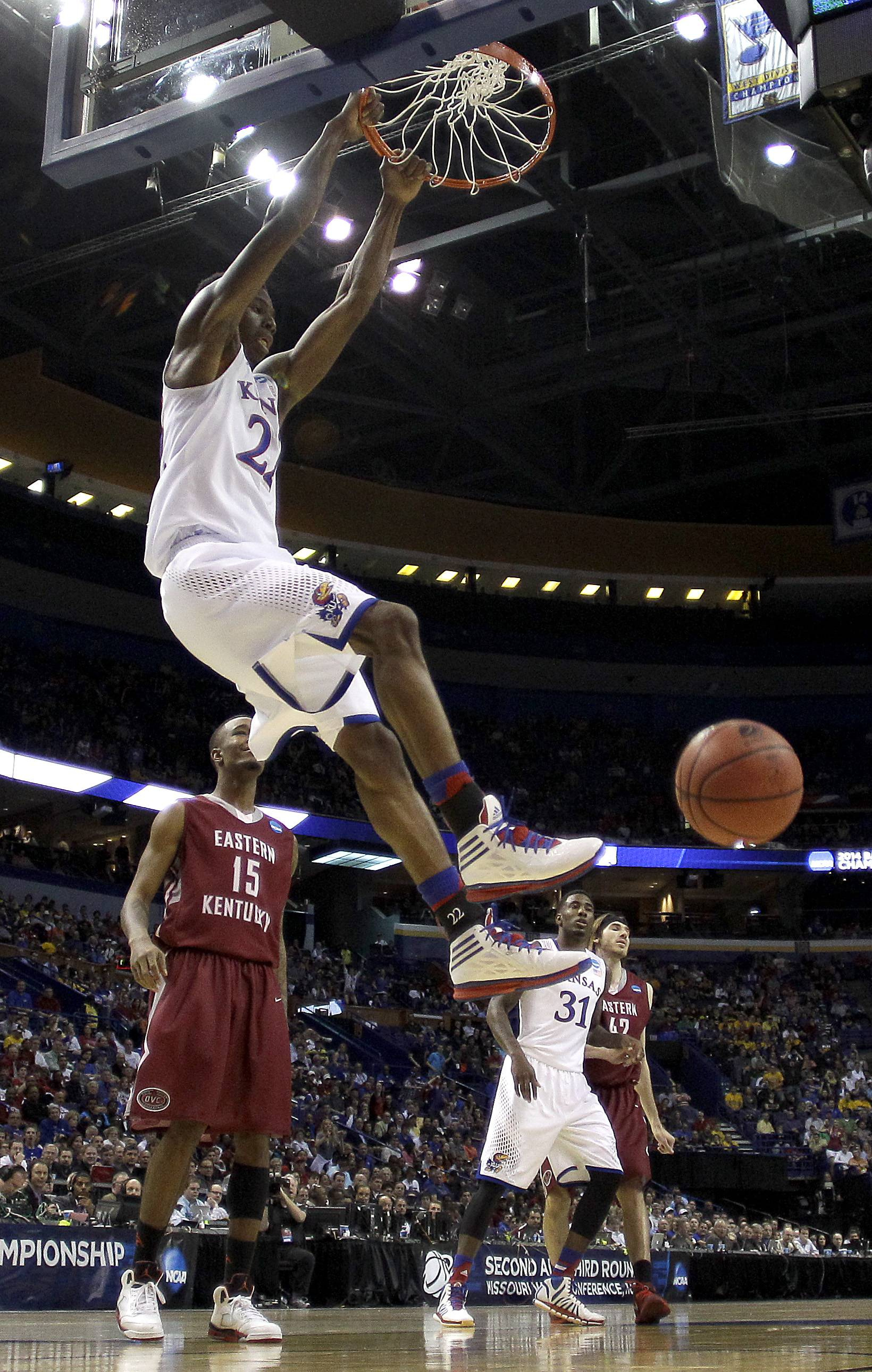 Kansas' Andrew Wiggins gets past Eastern Kentucky's Orlando Williams (15) to dunk the ball during the first half of a second-round game in the NCAA college basketball tournament, Friday, March 21, 2014, in St. Louis. Kansas won the game 80-69.