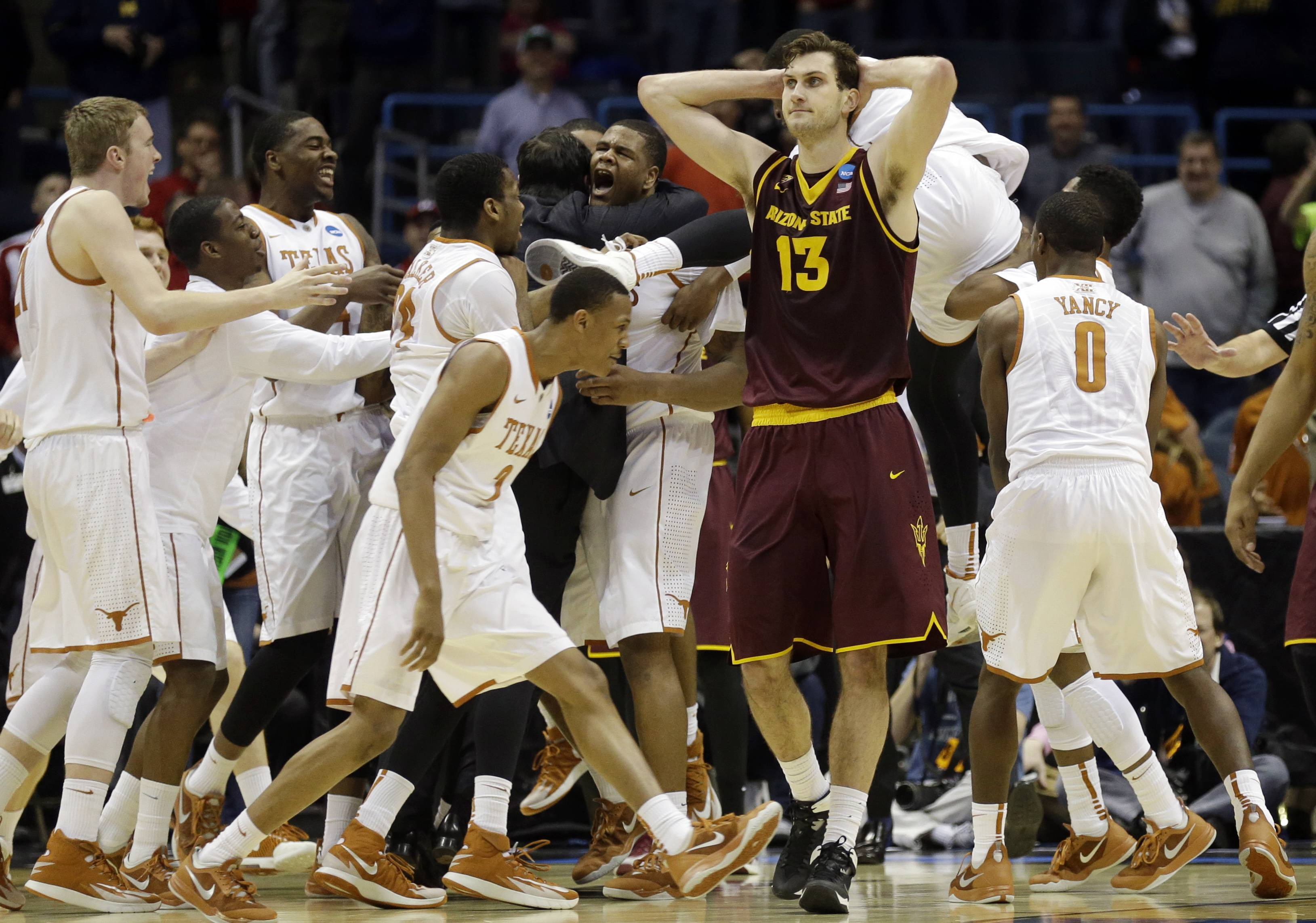 Texas players celebrates Cameron Ridley's game winning shot as Arizona State center Jordan Bachynski (13) walks off after a second-round game in the NCAA college basketball tournament Thursday, March 20, 2014, in Milwaukee. Texas won 87-85.