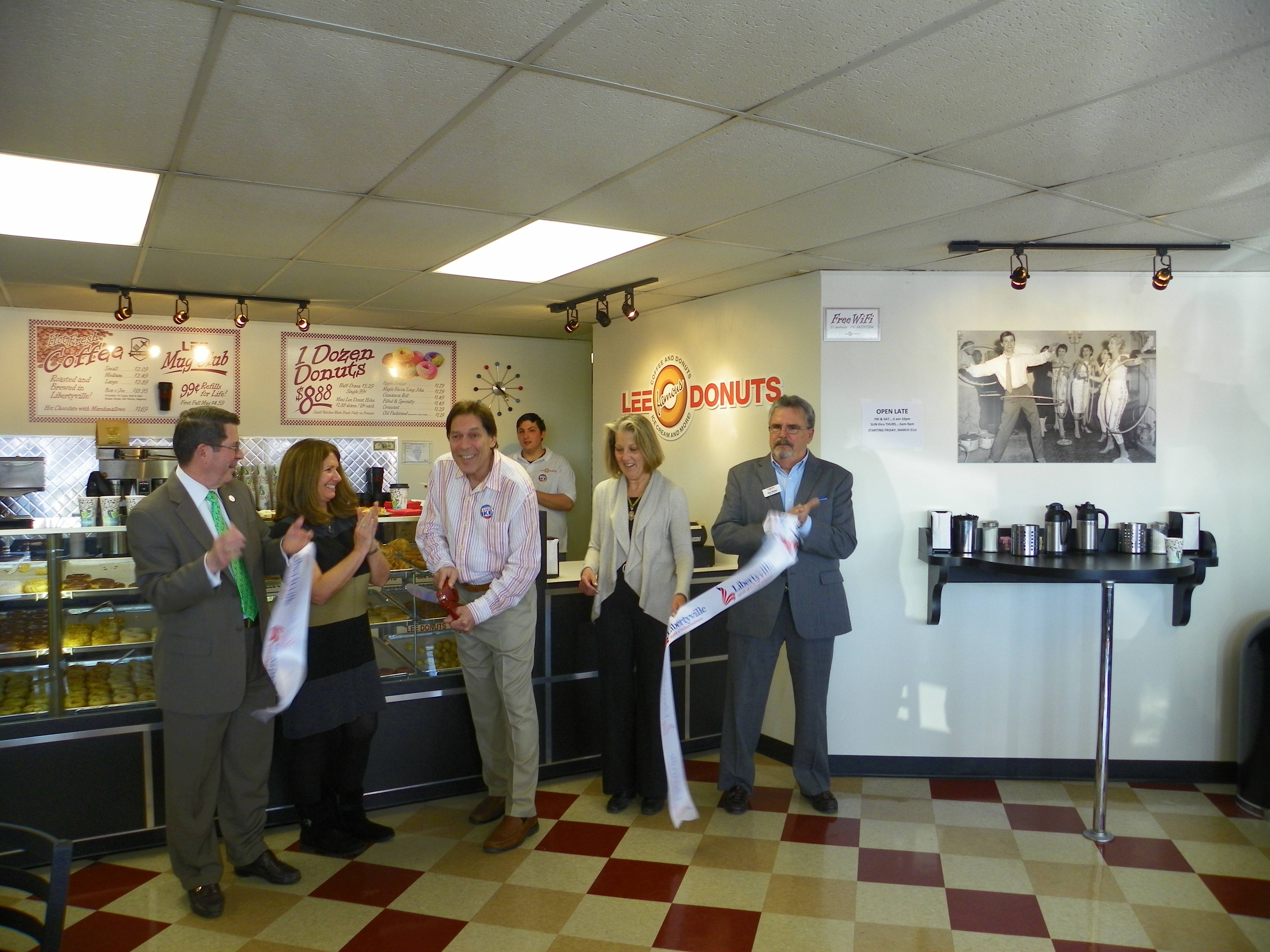 Bill Kaiser, new owner of LEE Famous Donuts cuts the ribbon with (Left to Right) Mayor Terry Weppler, Francine Kaiser (Bill's Wife), Pam Hume (Executive Director of MainStreet Libertyville) and Ray Mullen (Executive Director GLMV Chamber of Commerce) looking on.Bill Kaiser