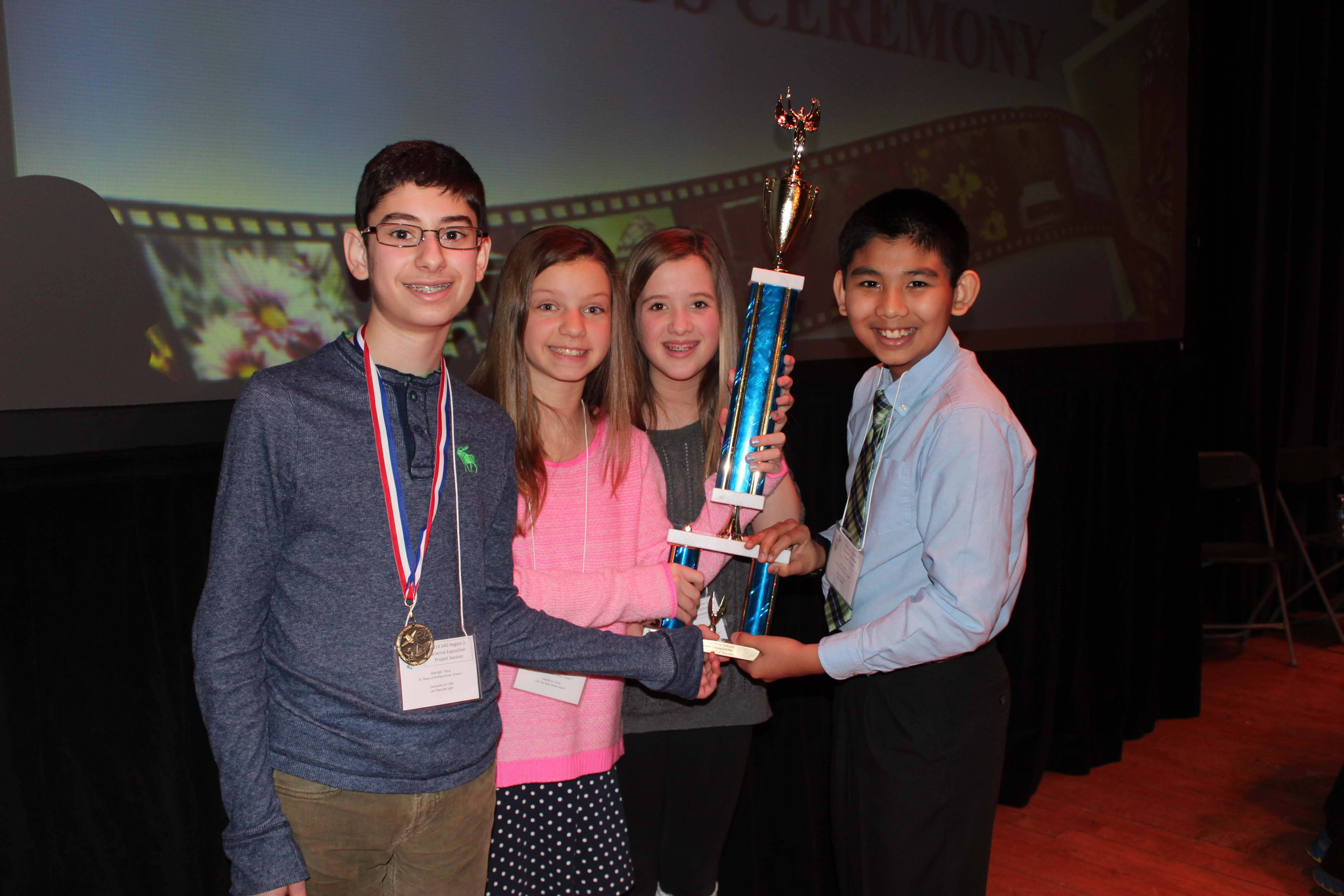 Saint Mary 7th graders, George Yacu (Wheeling), Ally Schwabe (Arlington Heights), Hailey Keenan (Buffalo Grove) and John Antony (Buffalo Grove)hold the Championship trophy for the Top School in the paper session.Lisa Schwabe, Saint Mary Public Relations